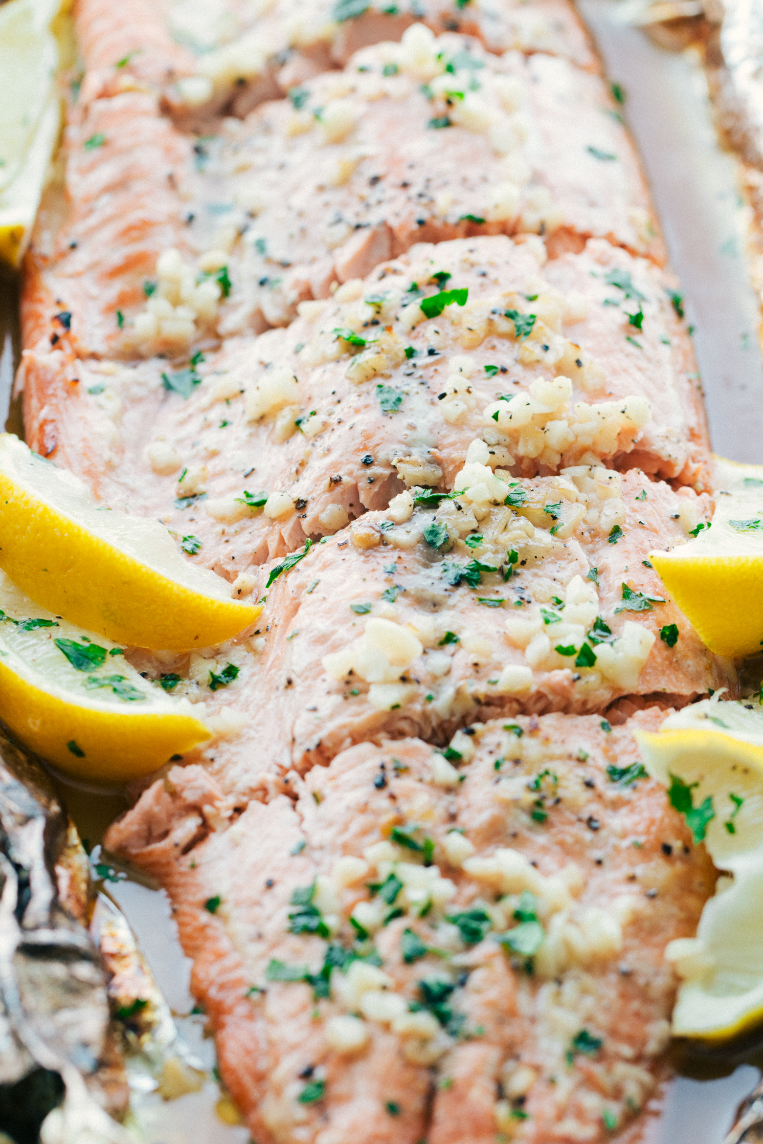 Garlic butter salmon baked on a piece of foil topped with lemon slices and chopped parsley by The Food Cafe.