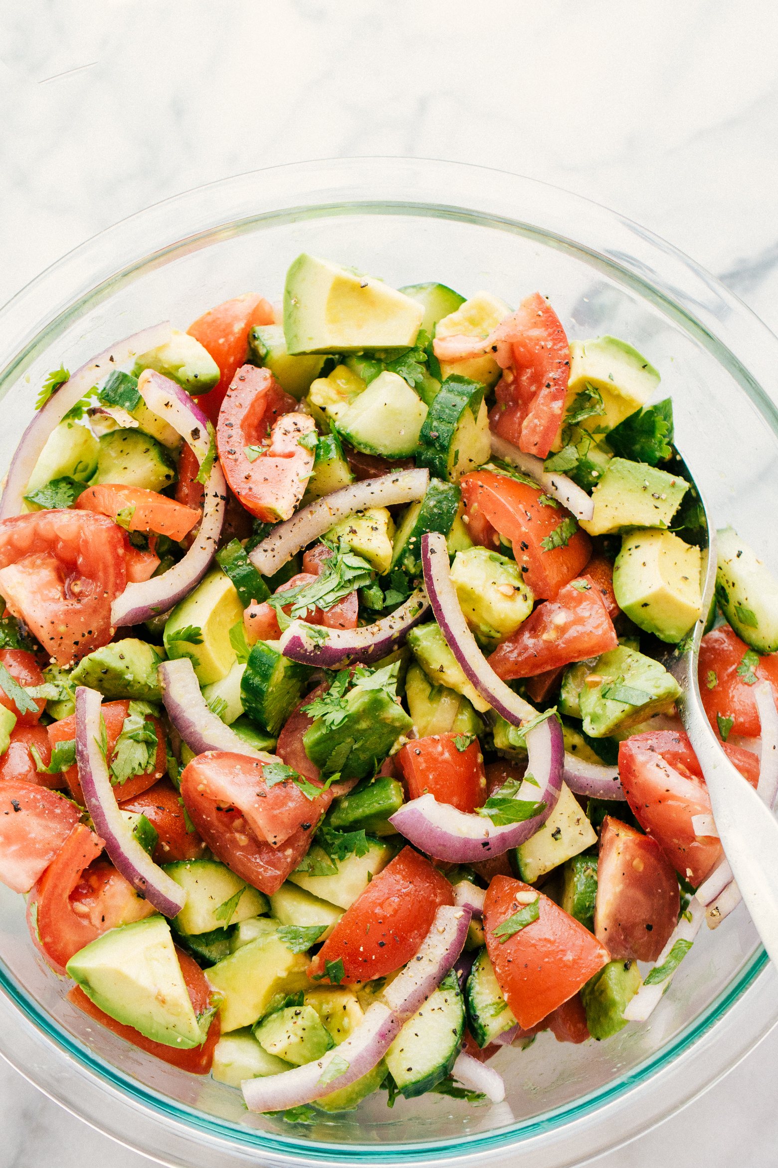 avocado tomato cucumber salad in a clear bowl with a spoon for serving.