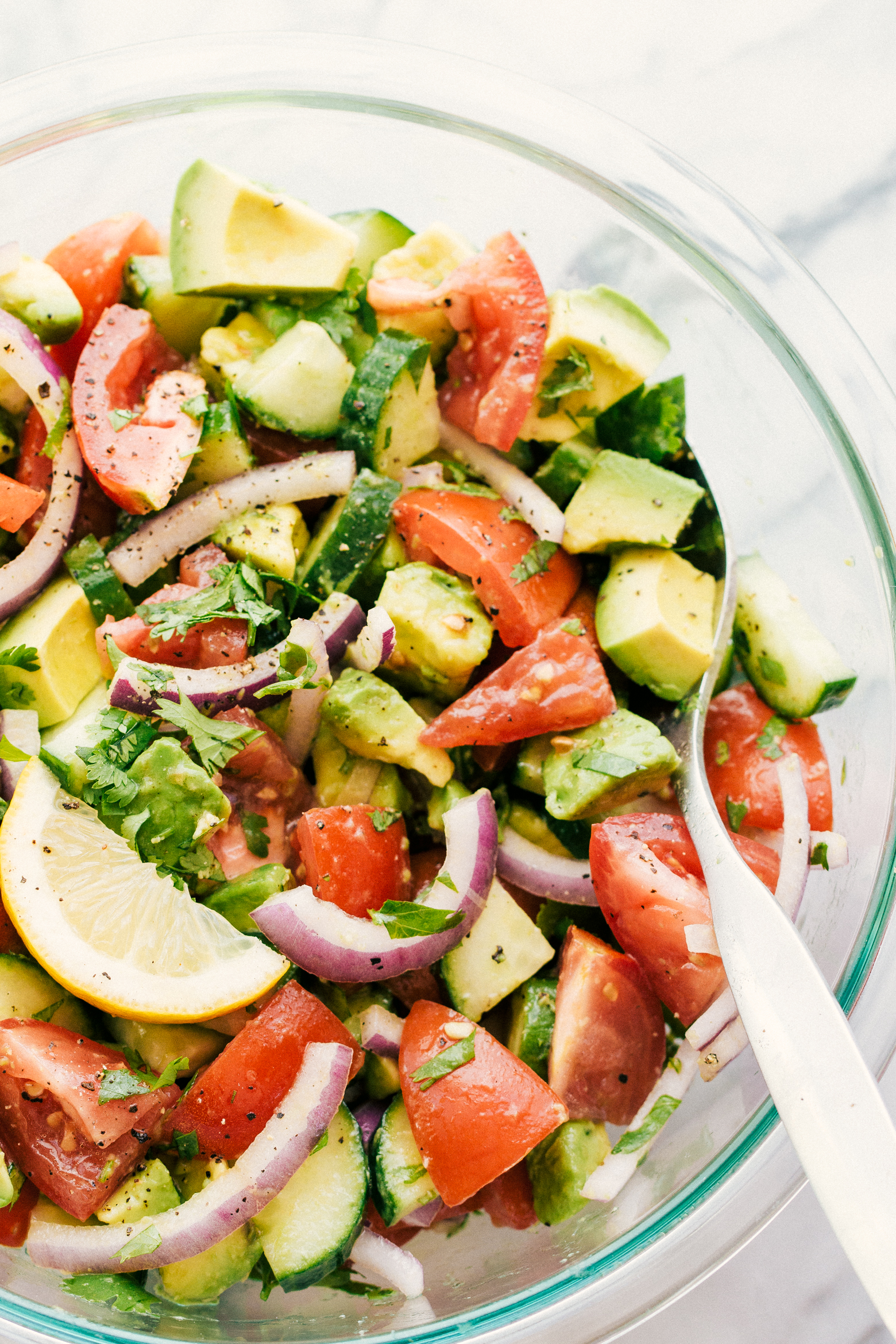 avocado tomato cucumber salad in a bowl garnished with sliced lemons ready to serve-simple and delicious recipe
