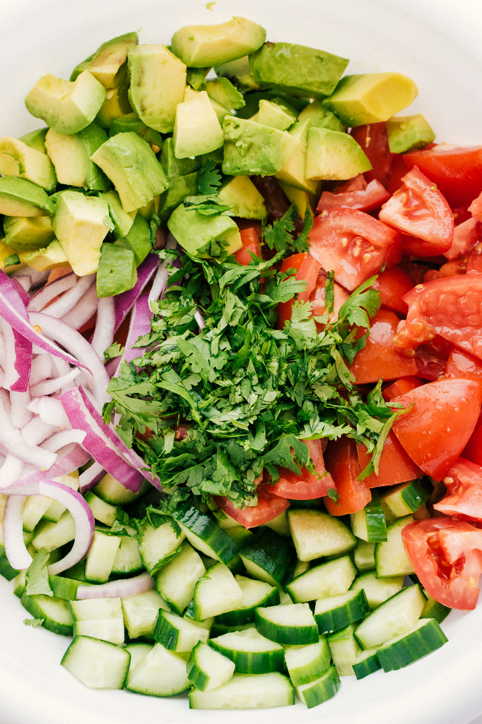 all the fresh ingredients chopped up to make avocado tomato cucumber salad