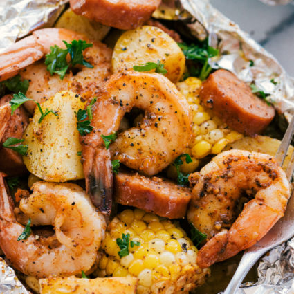 shrimp, corn, sausage, and potatoes cooked in foil with a fork for serving.