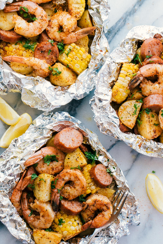 Shrimp boil foil packets served wit lemon slices ready to eat.