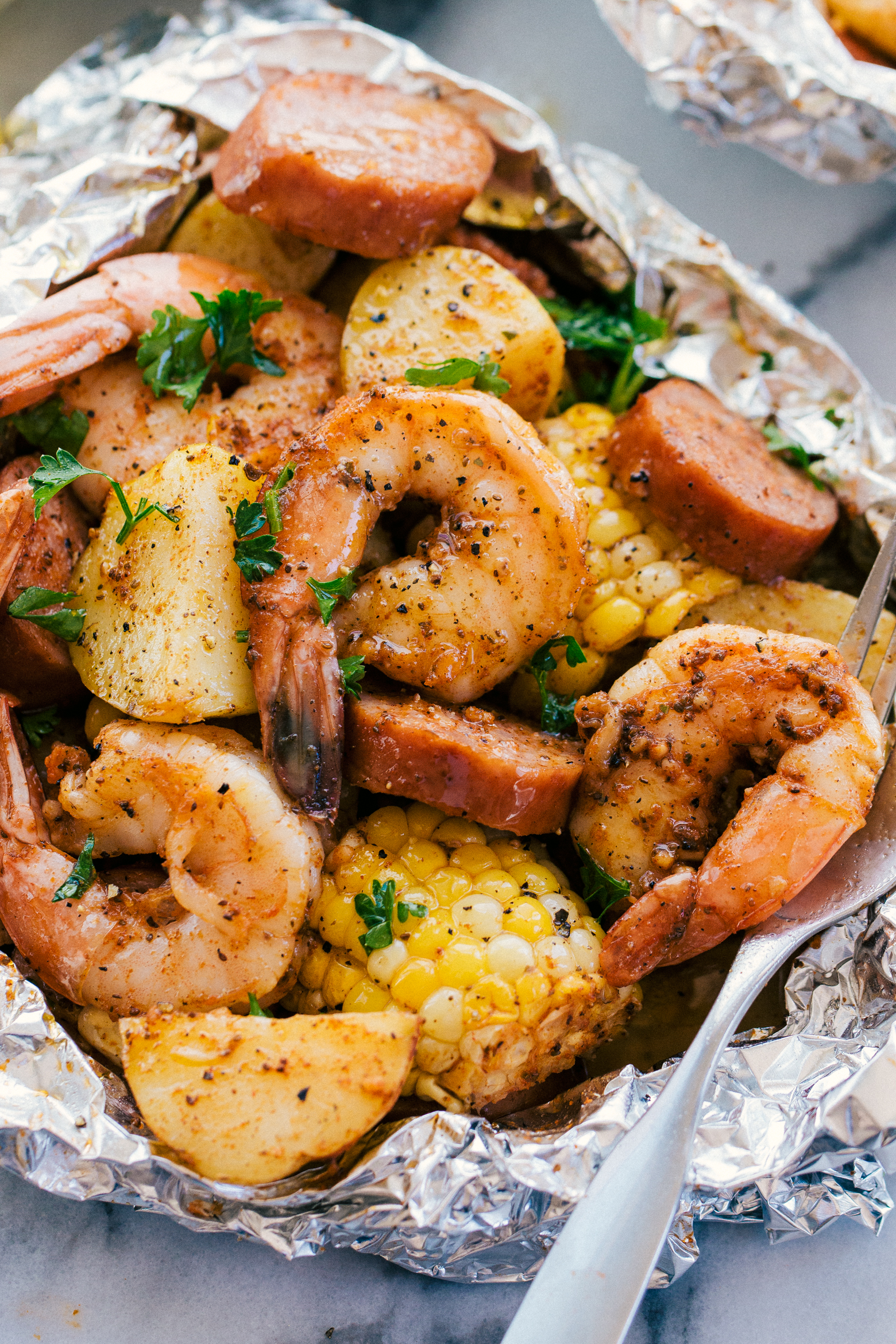 shrimp, corn, andouille sausage, and potatoes in foil with butter and parsley.