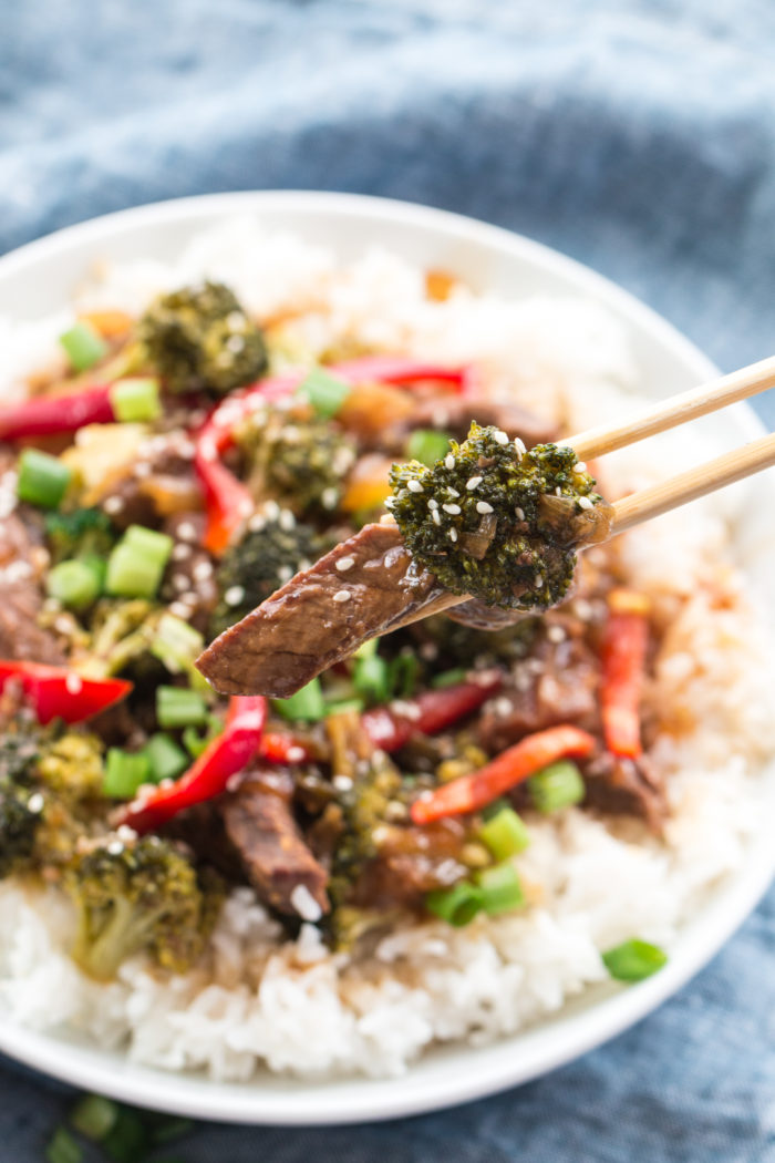slow cooker beef and broccoli being eaten with chop sticks out of a white bowl by The Food Cafe.