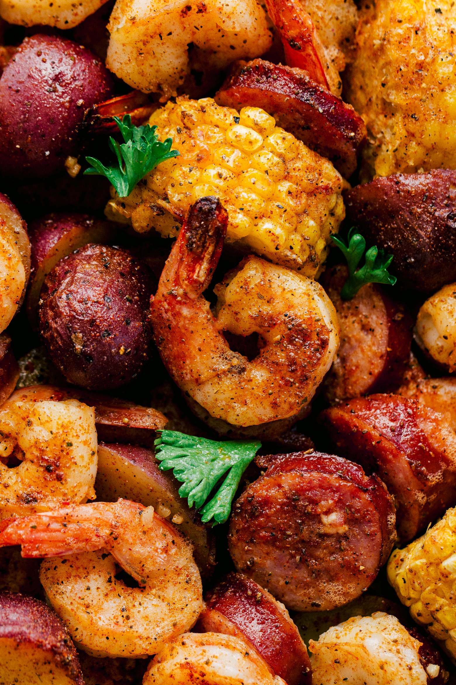 Shrimp boil recipe made on a sheet pan in the oven with corn, shrimp, sausage, and red potatoes, by The Food Cafe.