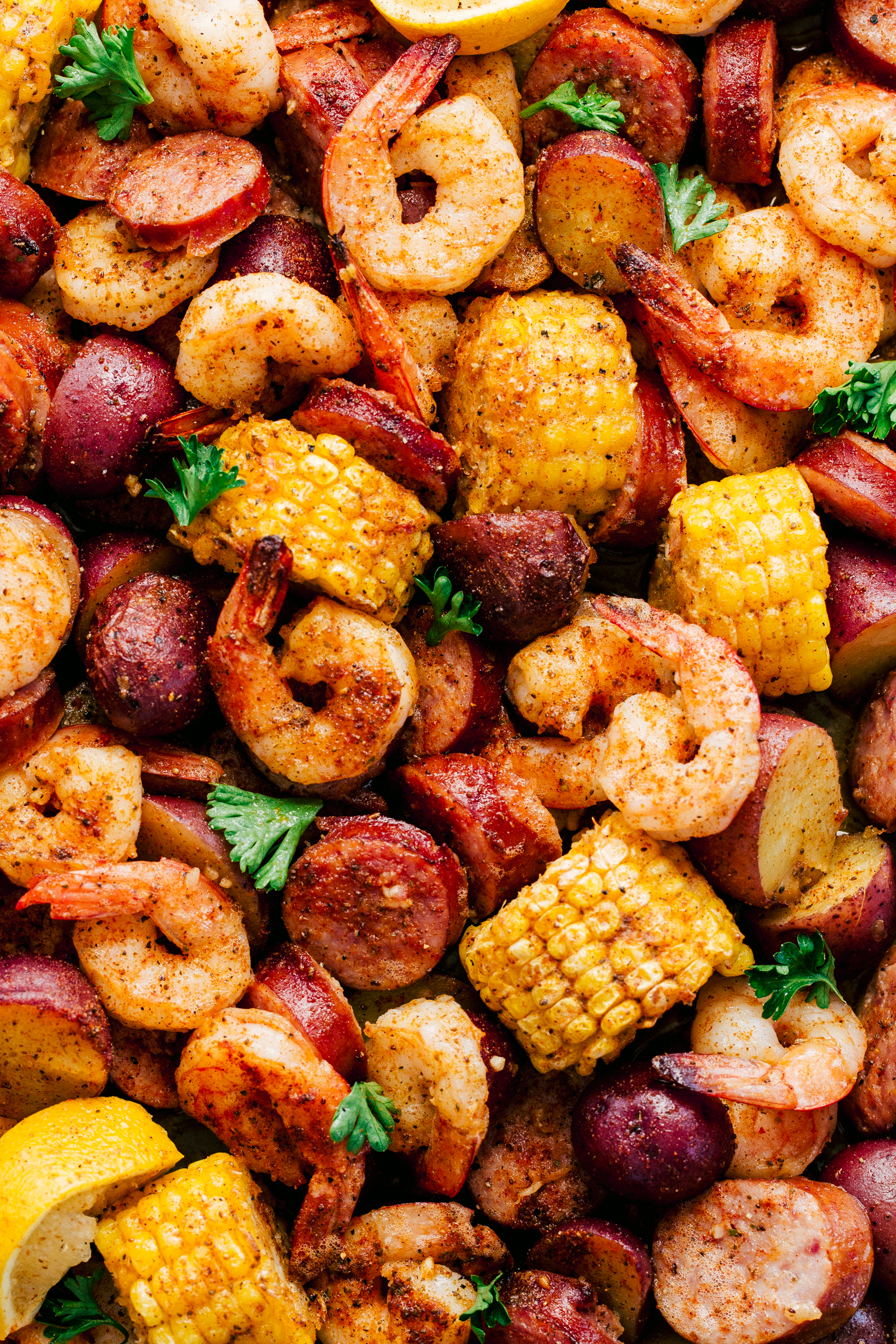 Garlic shrimp boil made in a sheet pan with sausage, corn, and red potatoes by The Food Cafe.