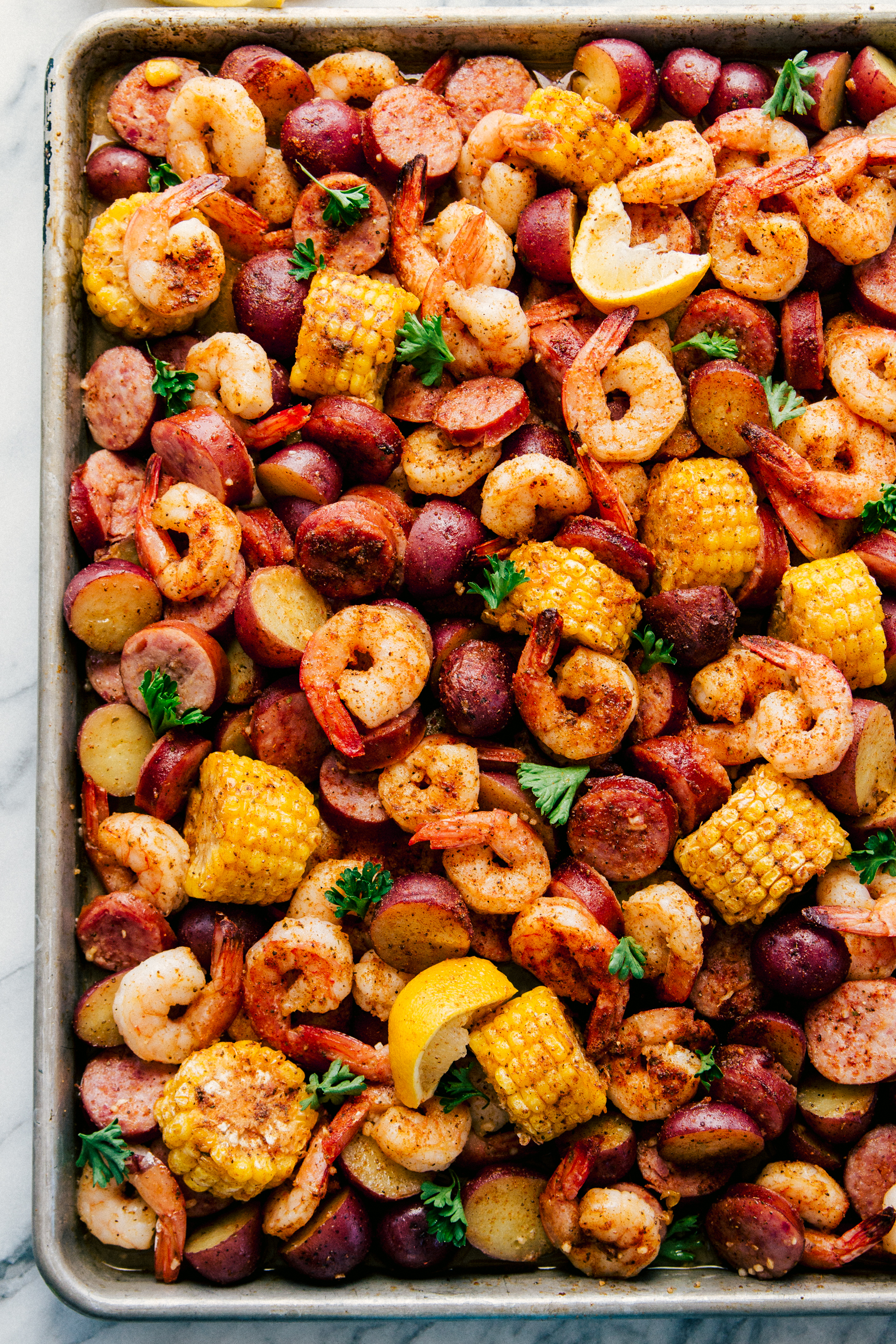 sheet pan garlic shrimp boil with sausage, corn, and red potatoes by The Food Cafe.