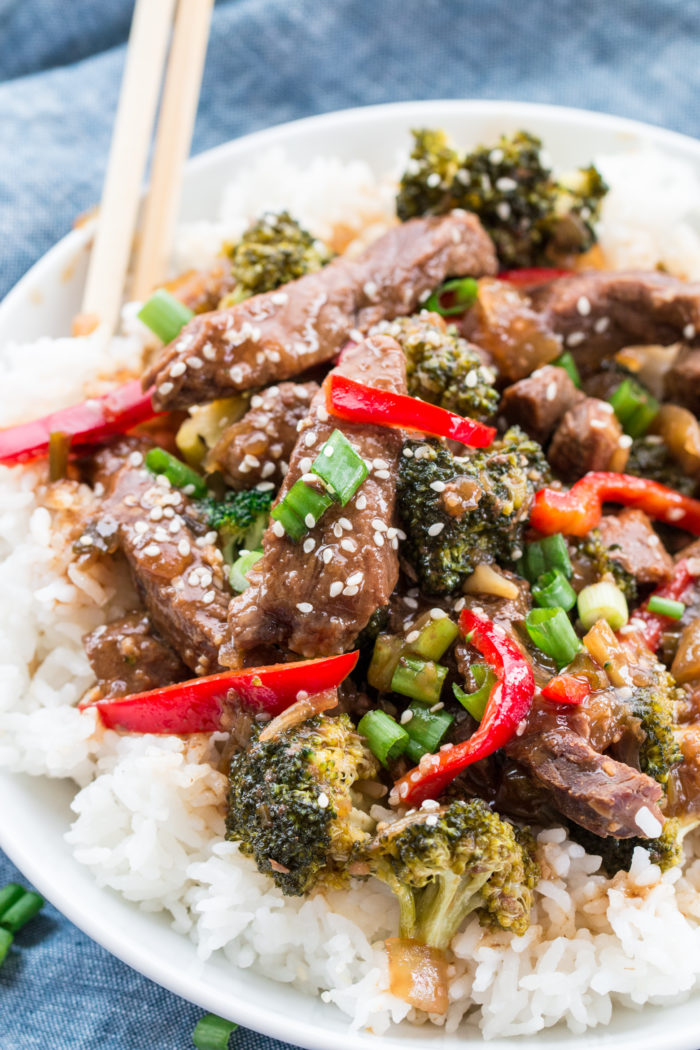 beef and broccoli on a bed of white rice topped with sesame seeds, chopped green onions and served with chop stick, by The Food Cafe.