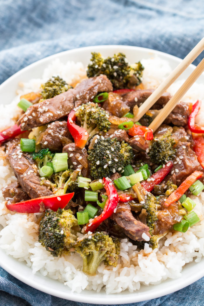 broccoli and beef mixed with sliced red peppers served over white rice in a white bowl, by The Food Cafe.