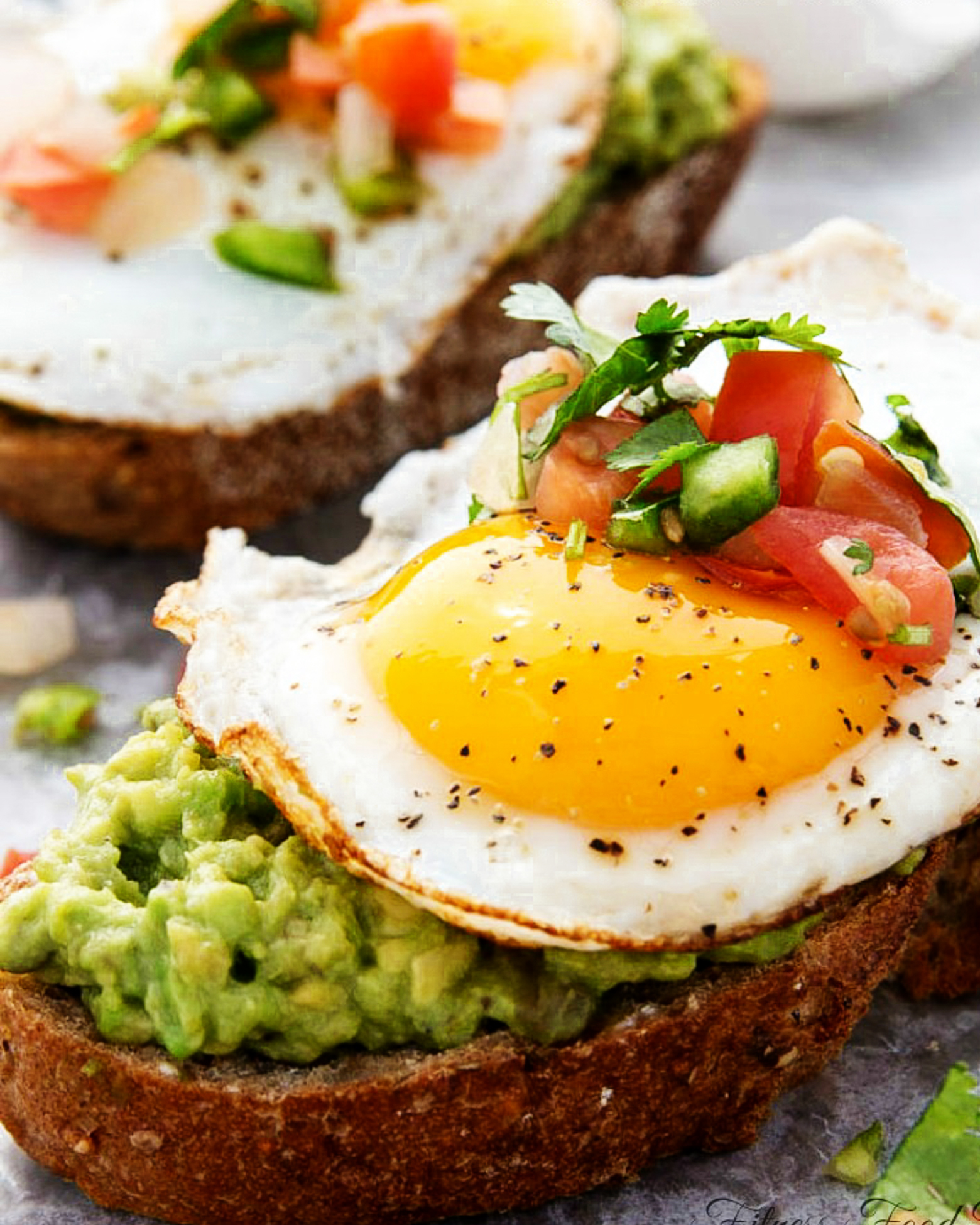 Avocado Toast with Egg topped with salt, pepper and pico de gallo.