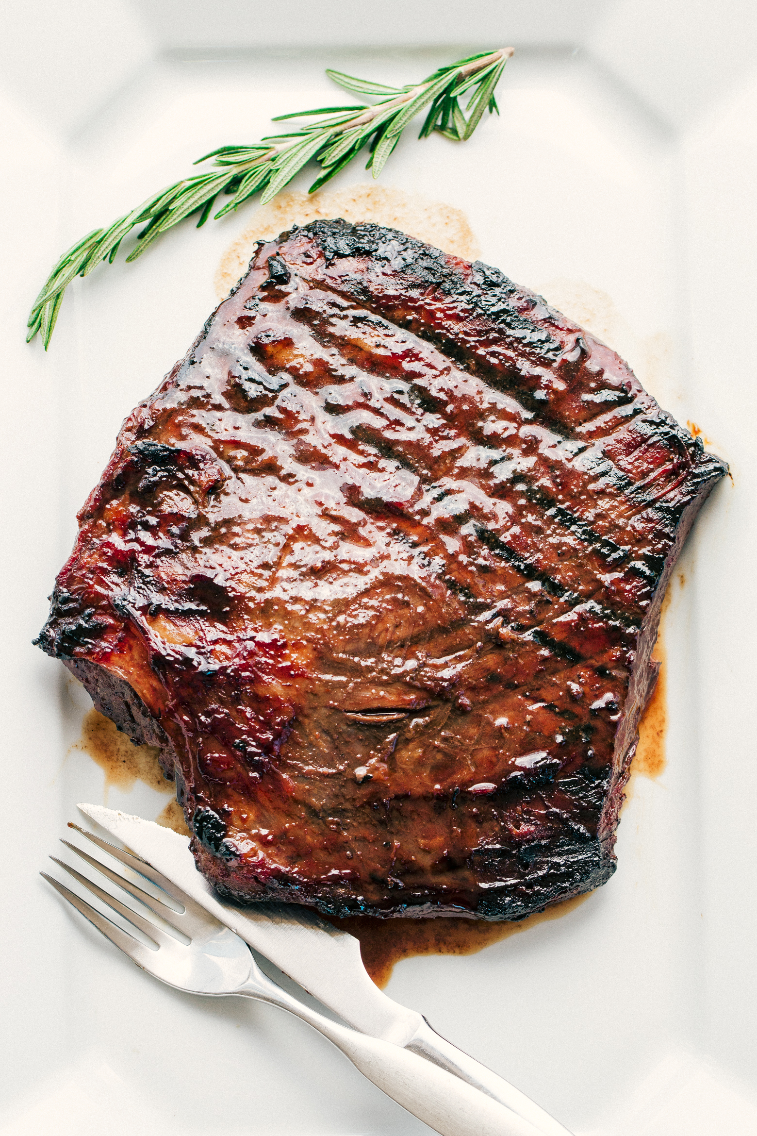 Flank Steak marinated and BBQd and placed on a white serving platter by The Food Cafe