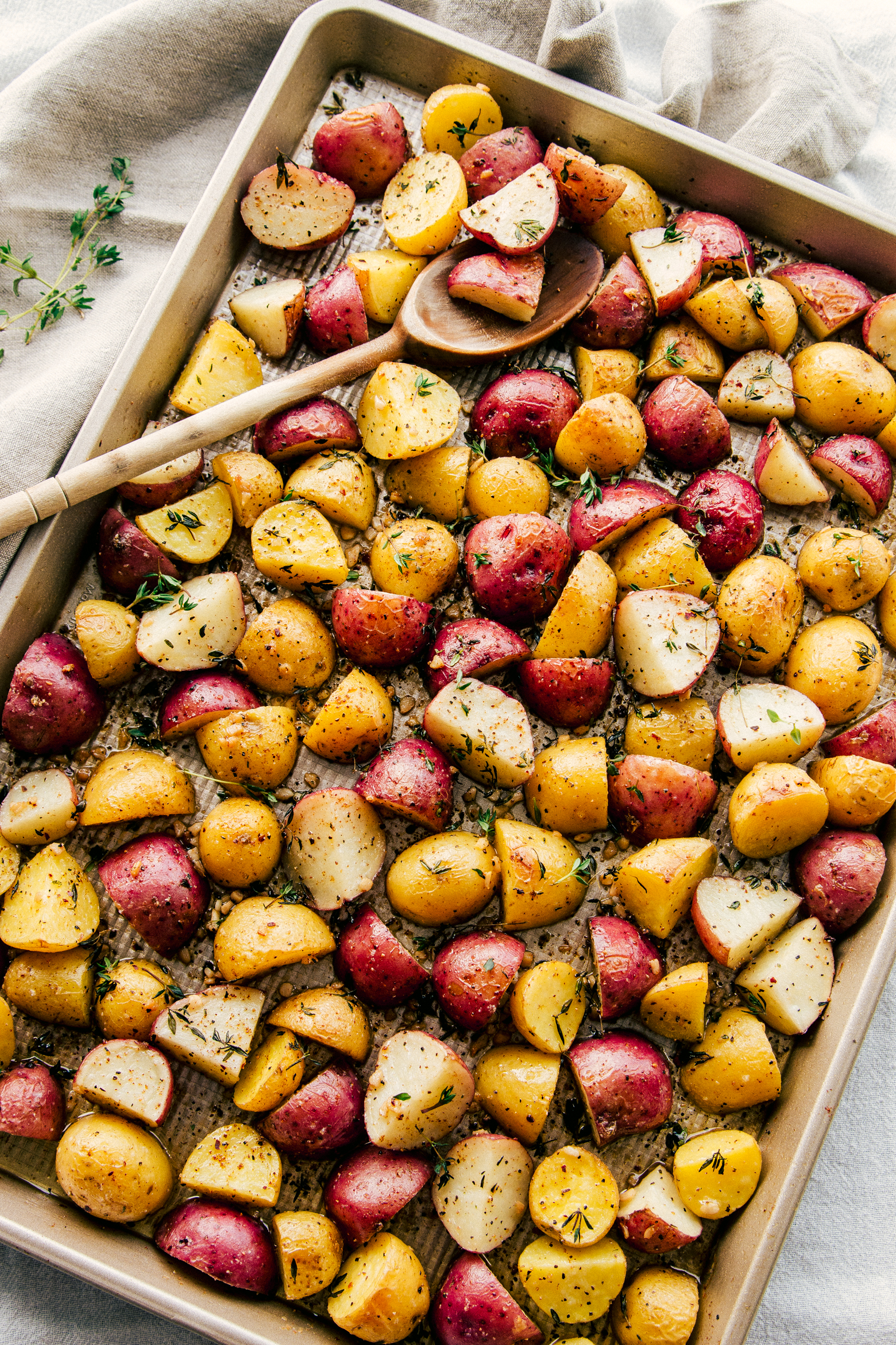 Garlic Butter Roasted Potatoes on a sheet pan with a wooden spoon for serving.