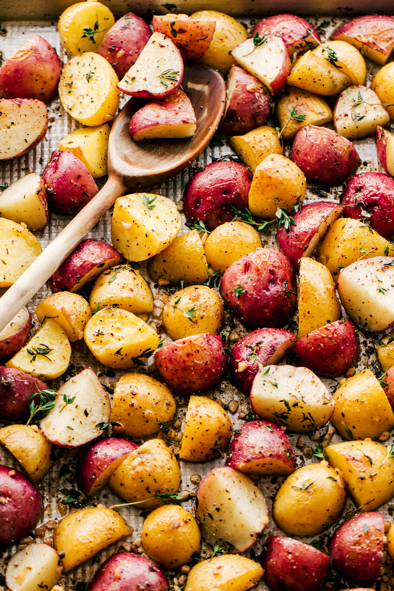 Roasted Potatoes on a sheet pan with a wooden spoon for serving topped with garlic butter and chopped rosemary by The Food Cafe