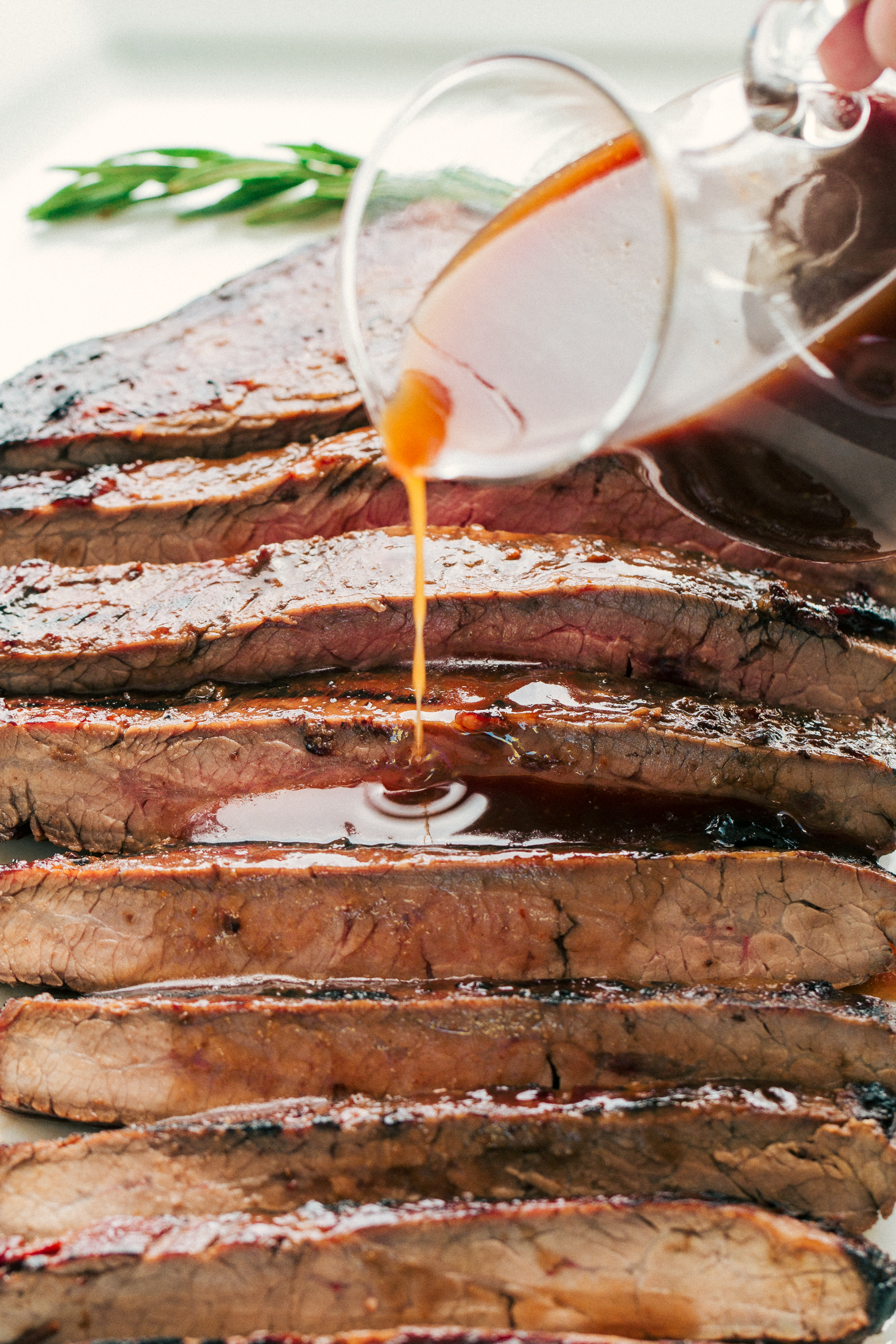 The best flank steak recipe being topped with a delicious marinade, perfect for dinner any night by The Food Cafe.