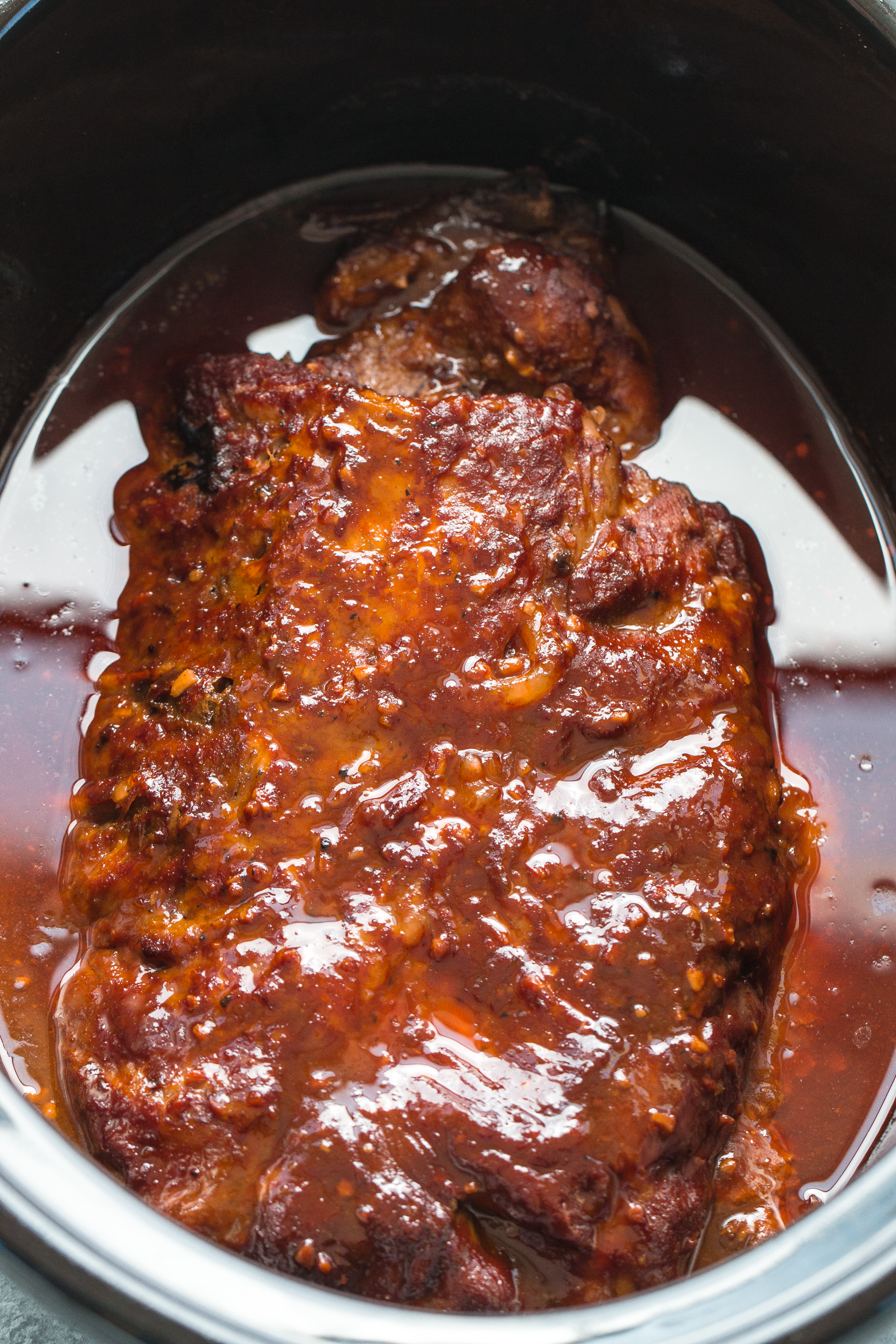 ribs in slow cooker cooked in bbq sauce for the perfect fall off the bone ribs by The Food Cafe.