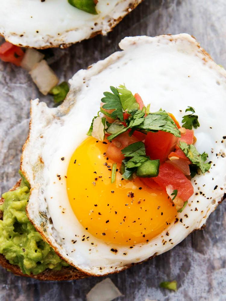 avocado toast with fried egg topped with pico de gallo.