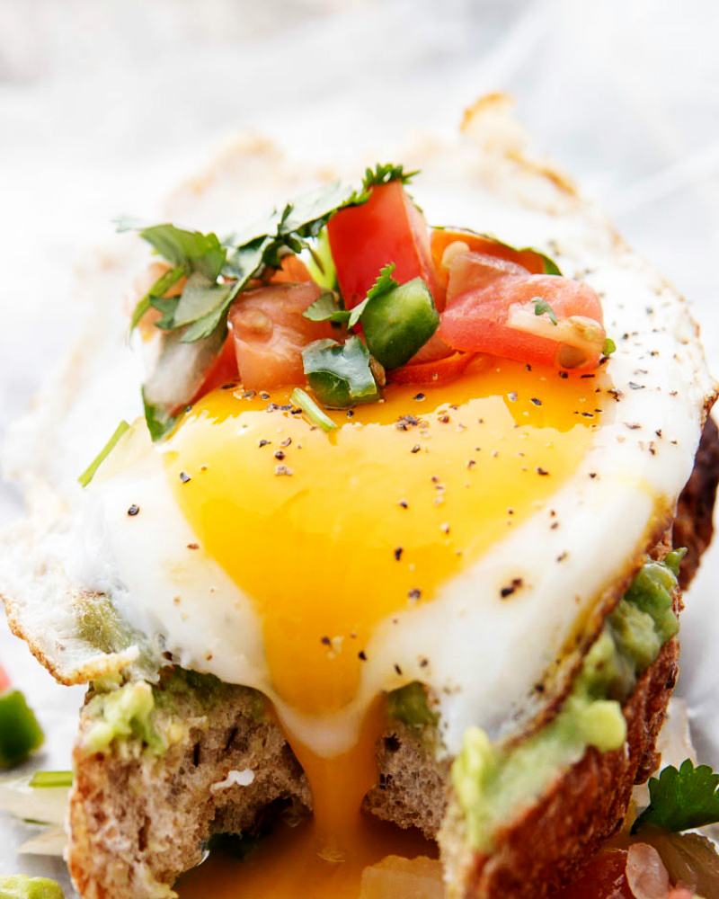 Avocado Egg Toast with a bite out of it with the yolk running out.