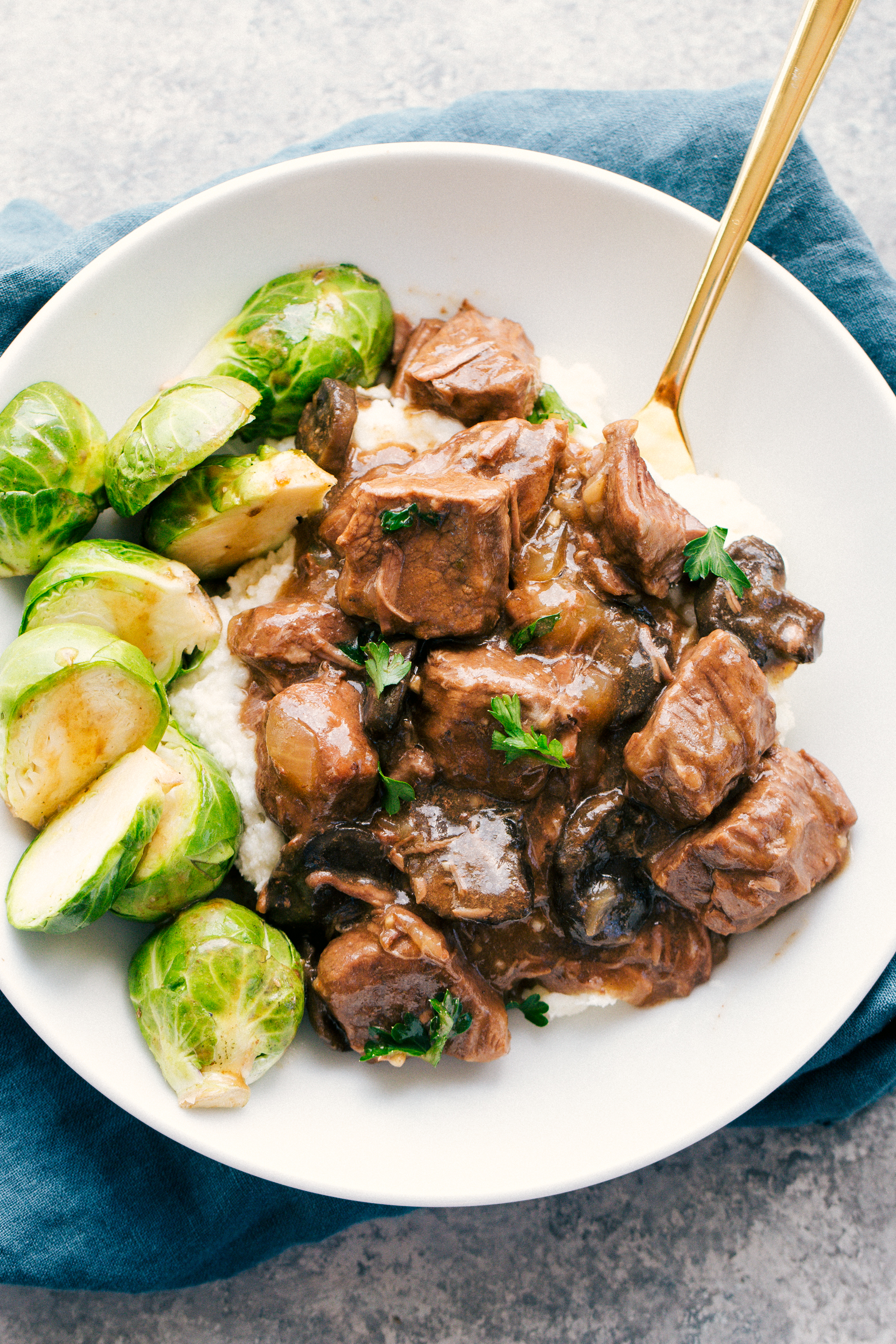 Slow cooker beef tips and gravy served over rice along side steamed brussels sprouts in a white bowl, by The Food Cafe.