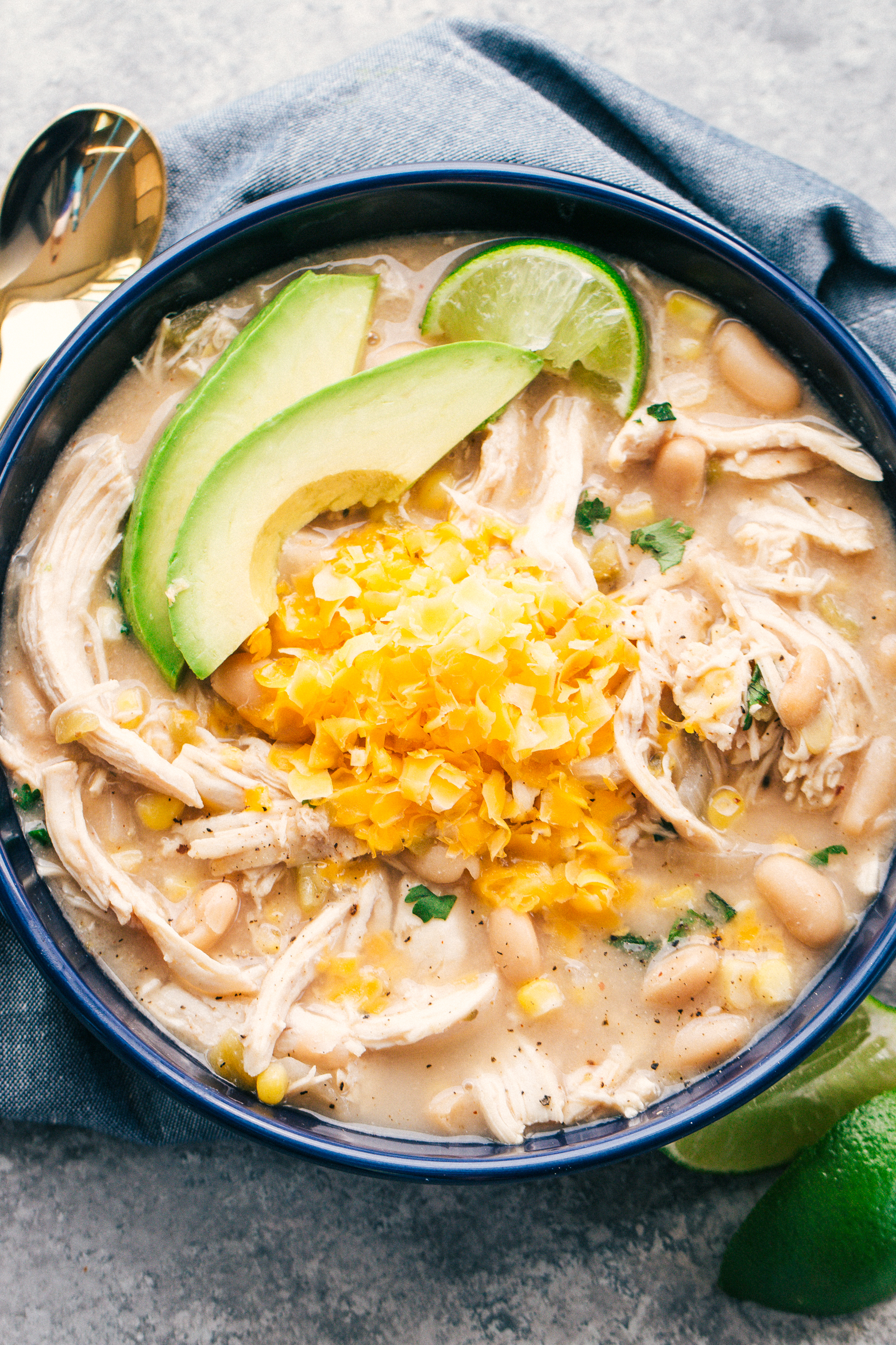white bean chicken chili recipe in a blue bowl on a light grey background served with a gold spoon, by The Food Cafe.