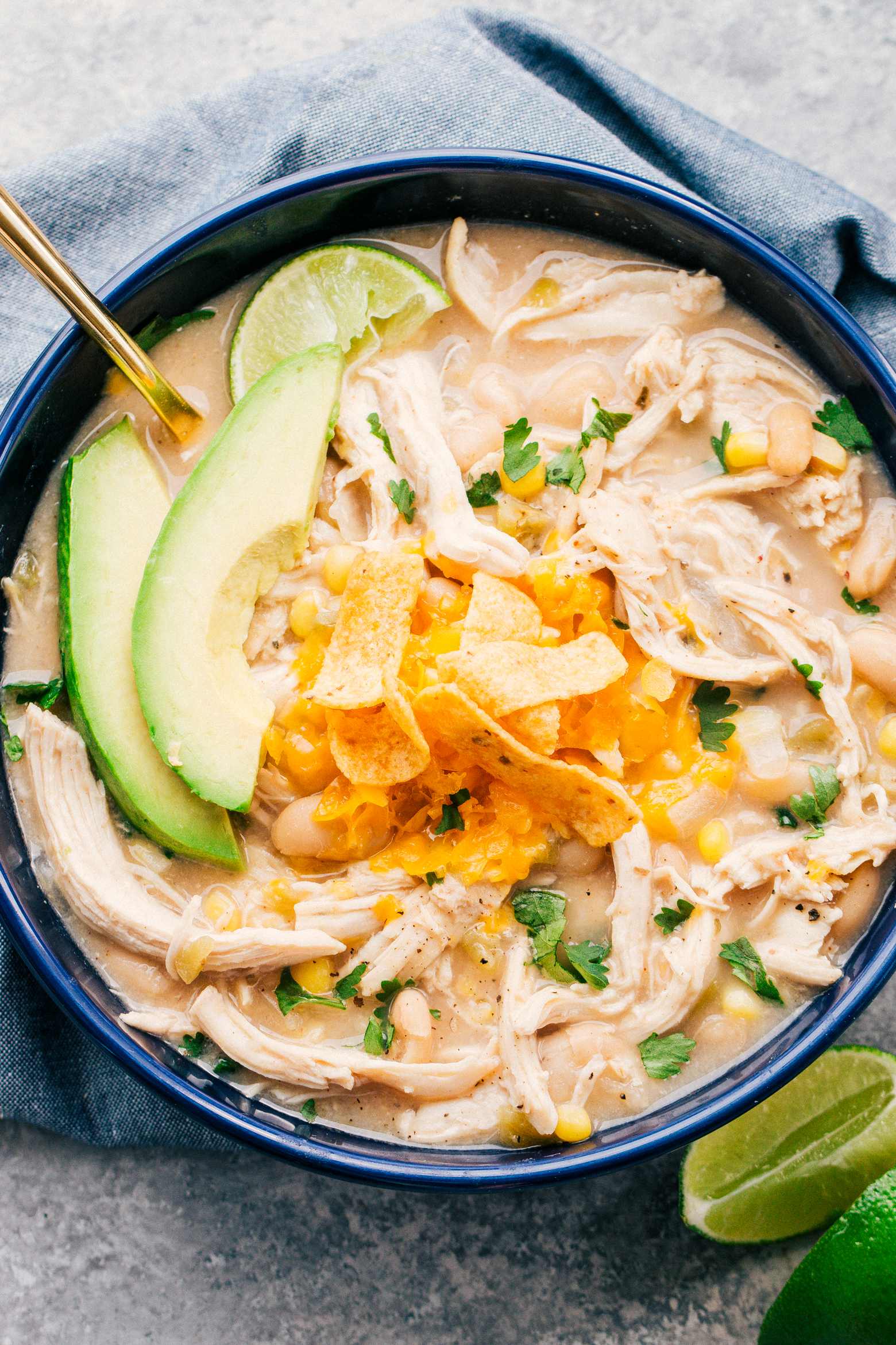 white bean chicken chili in a blue bowl served with sliced avocado and frito chips on top by The Food Cafe