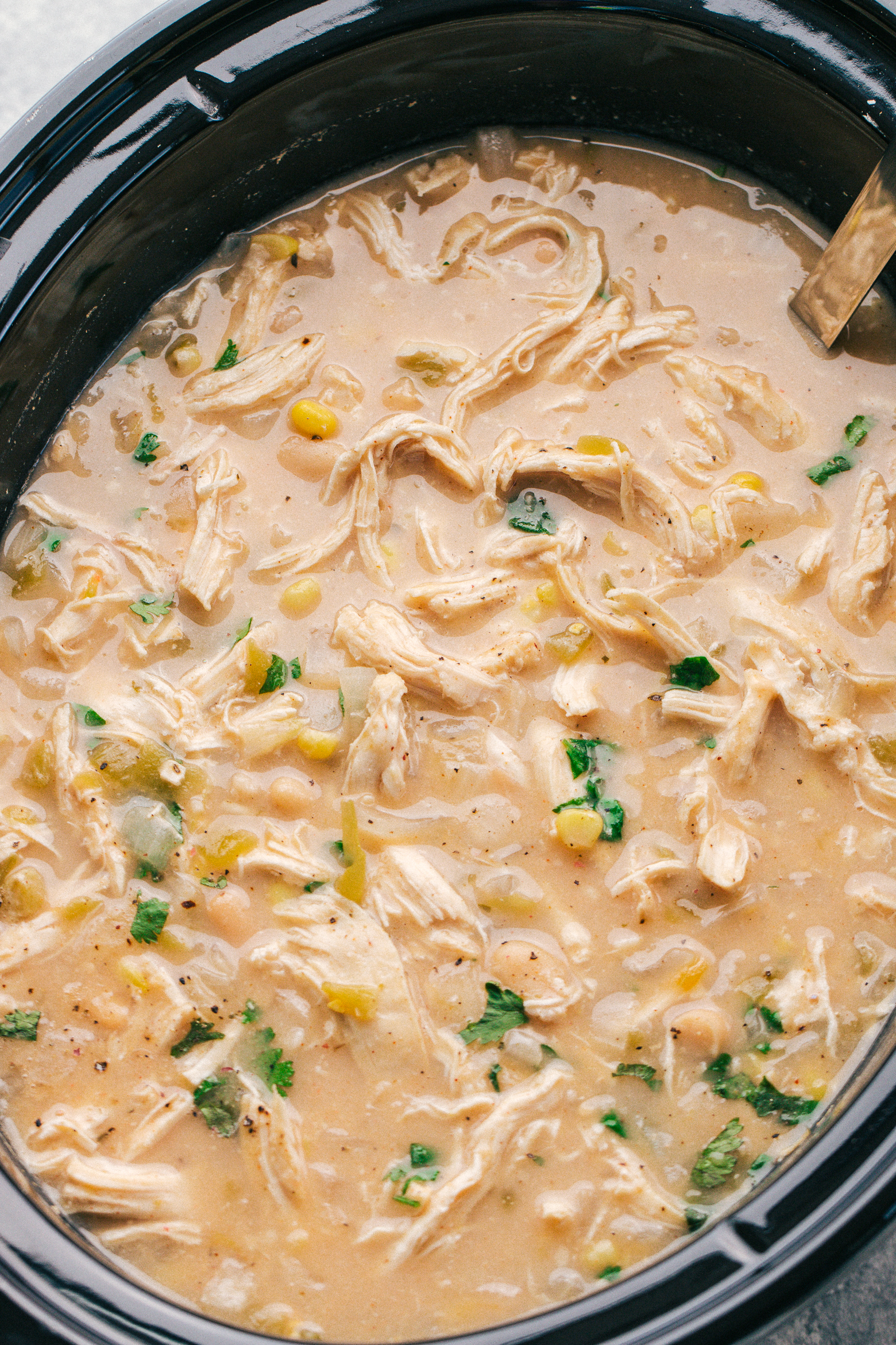 white bean chicken chili in a black crockpot perfect for a cold weekend at home, by The Food Cafe.