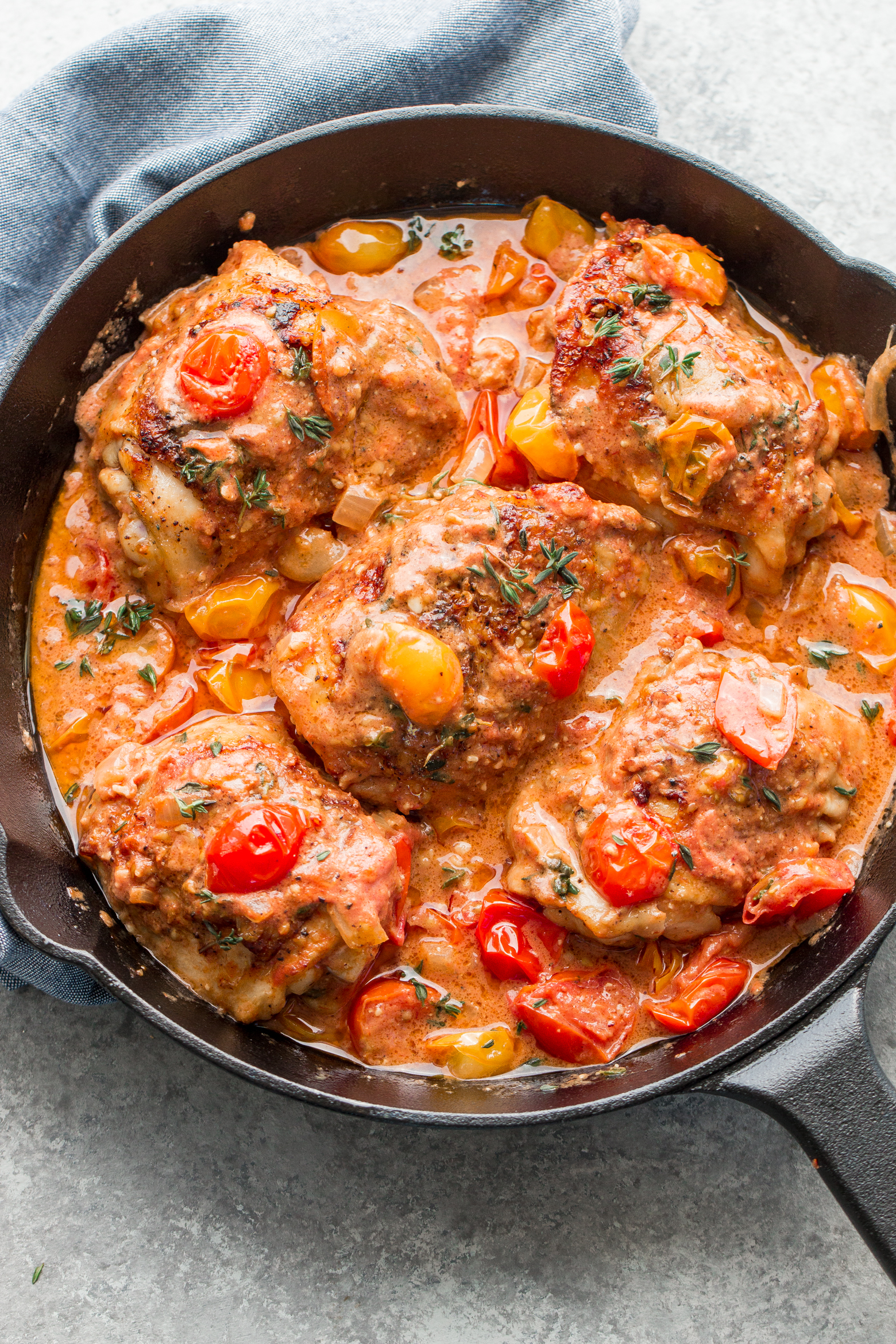 Garlic Chicken made in a skillet with a rich and creamy sauce and fresh tomatoes, by the food cafe.