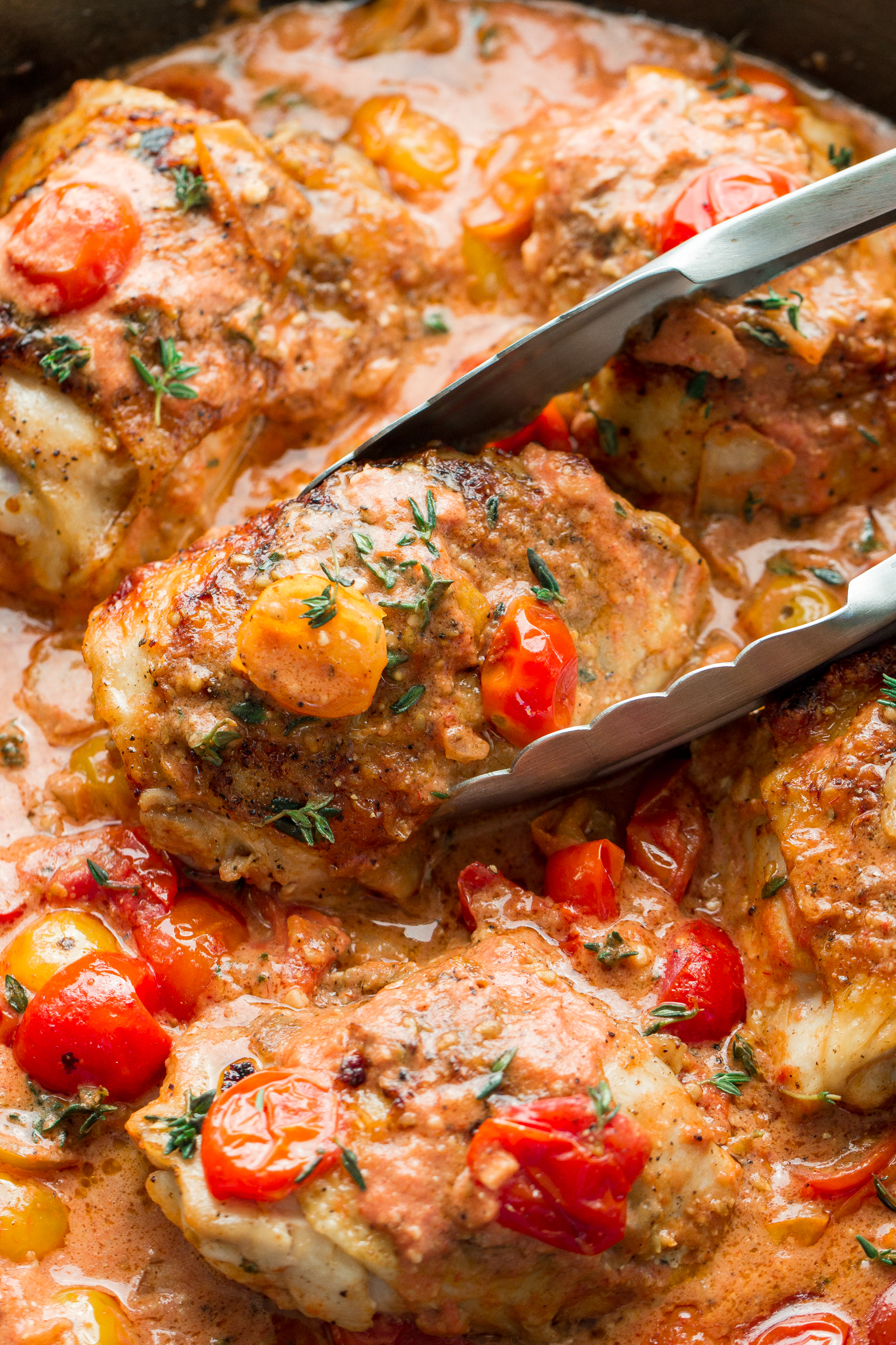 Creamy Garlic Chicken in a skillet made with fresh tomatoes in a creamy sauce by the food cafe