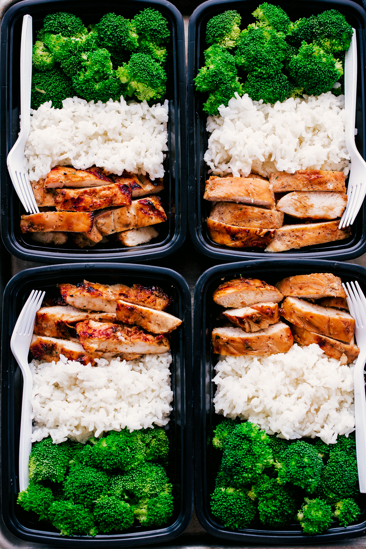 Teriyaki chicken meal prep in black containers served with white rice and steamed broccoli, simple and healthy by The Food Cafe.