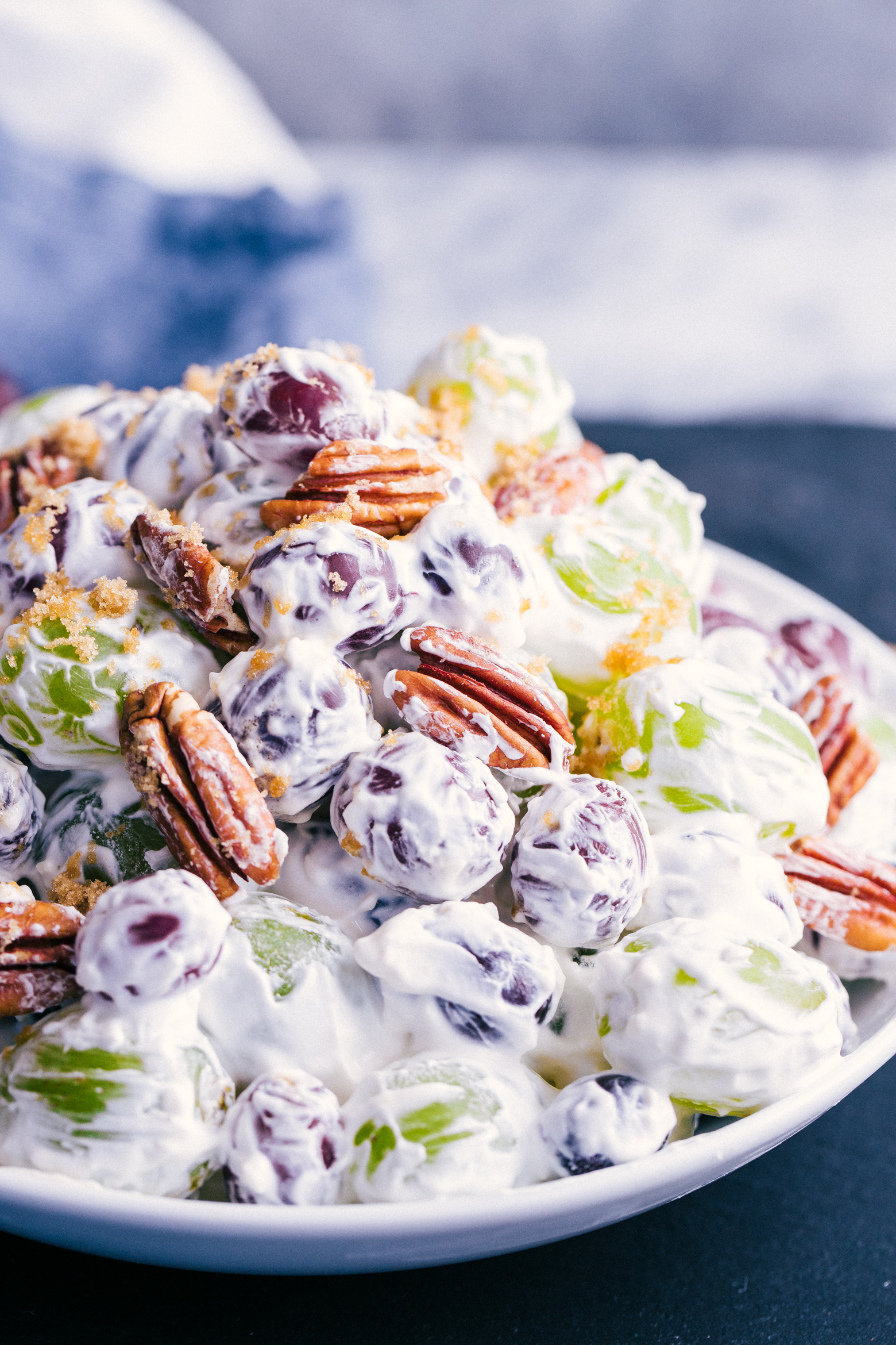 grape salad mixed in a creamy cool whip and cream cheese fluff served in a white bowl.