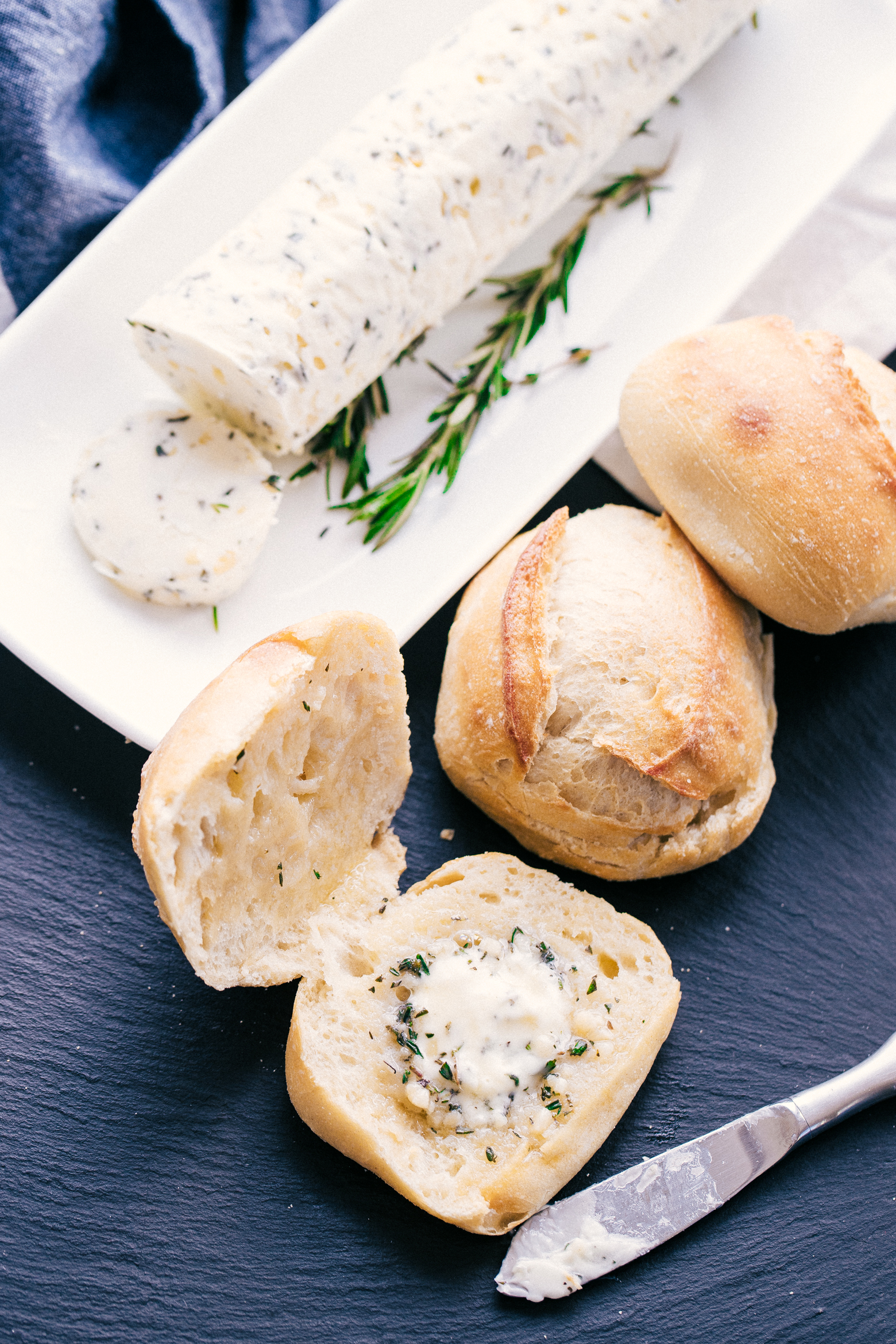 compound butter on a white plate with a slice cut off resting on plate.  Three rolls on dark background next to compound butter one cut open with herb compound butter spread on it.