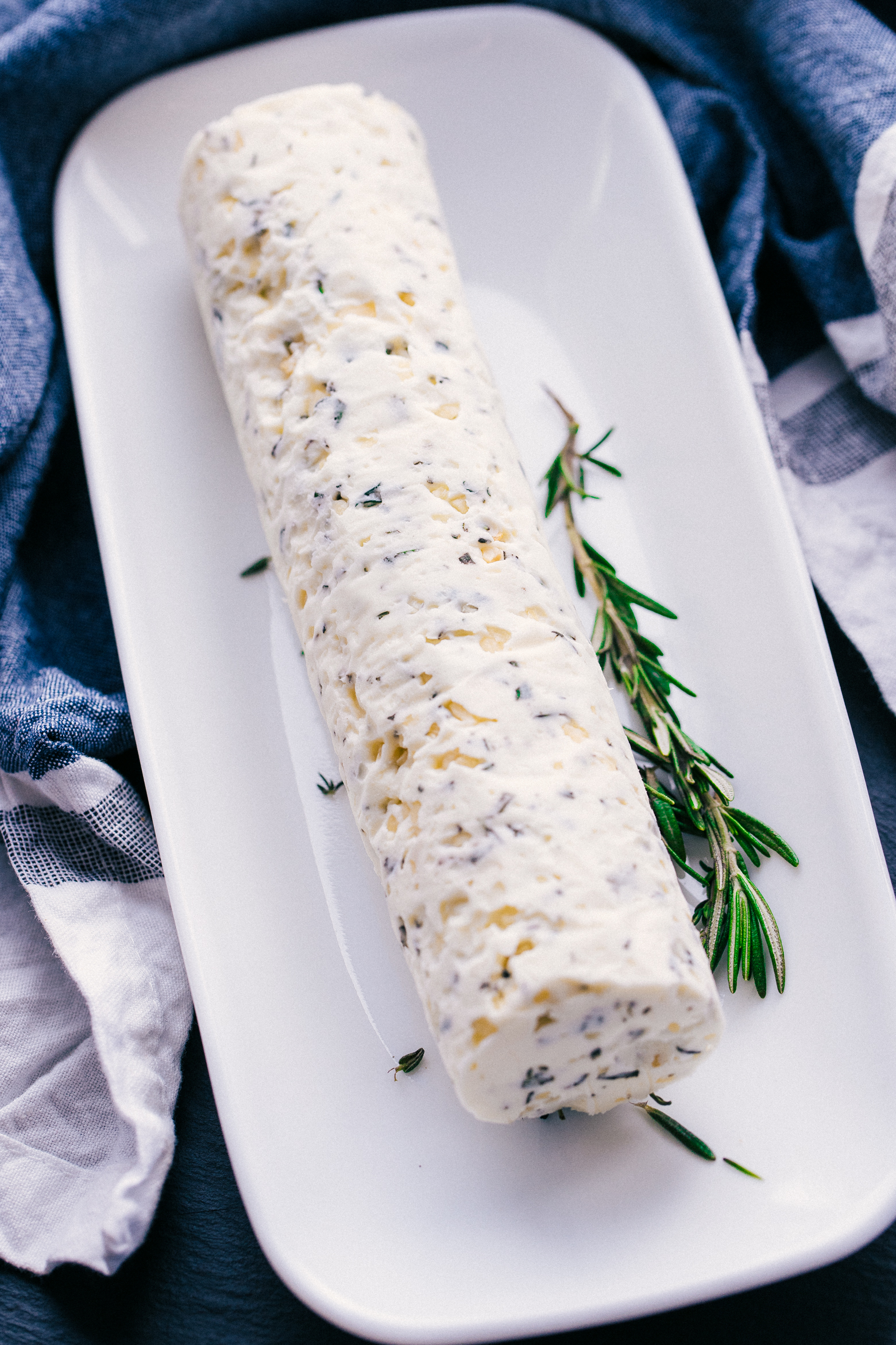 compound butter on a white serving platter with a garnish of rosemary along side with a soft blue background.