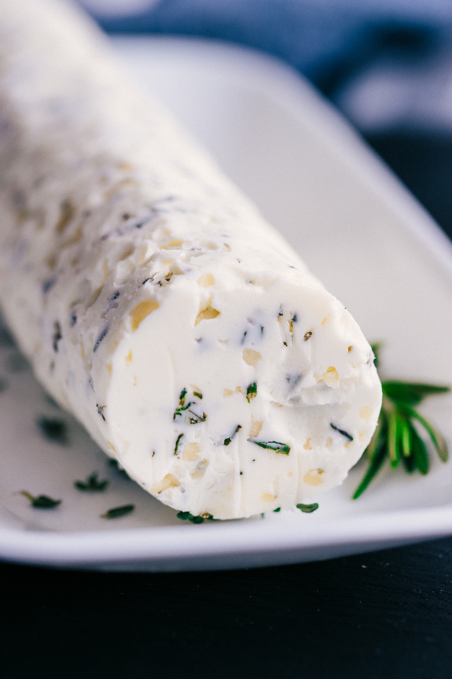 A close up of the compound butter on a white serving platter, showing the delicious herbs its made with-perfect on steak.