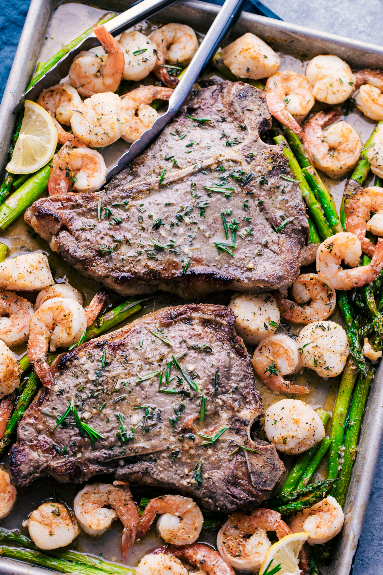 Steak, shrimp, and scallop surf and turf on a sheet pan served with asparagus by The Food Cafe