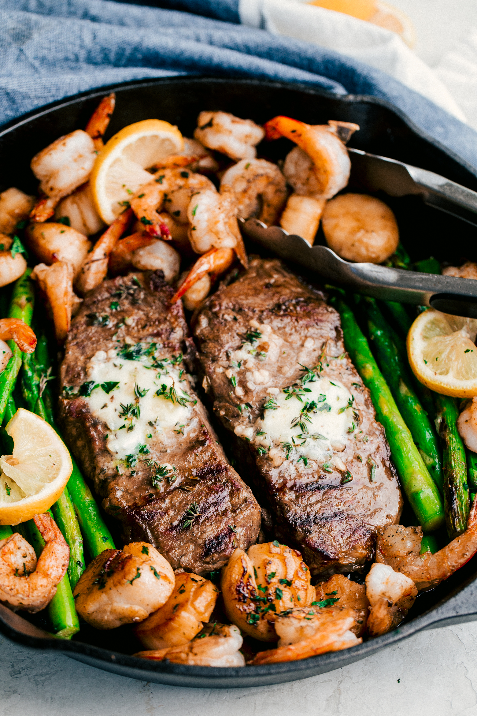 Garlic butter surf and turf made with roasted asparagus in a skillet topped with garlic butter and fresh herbs, by The Food Cafe.