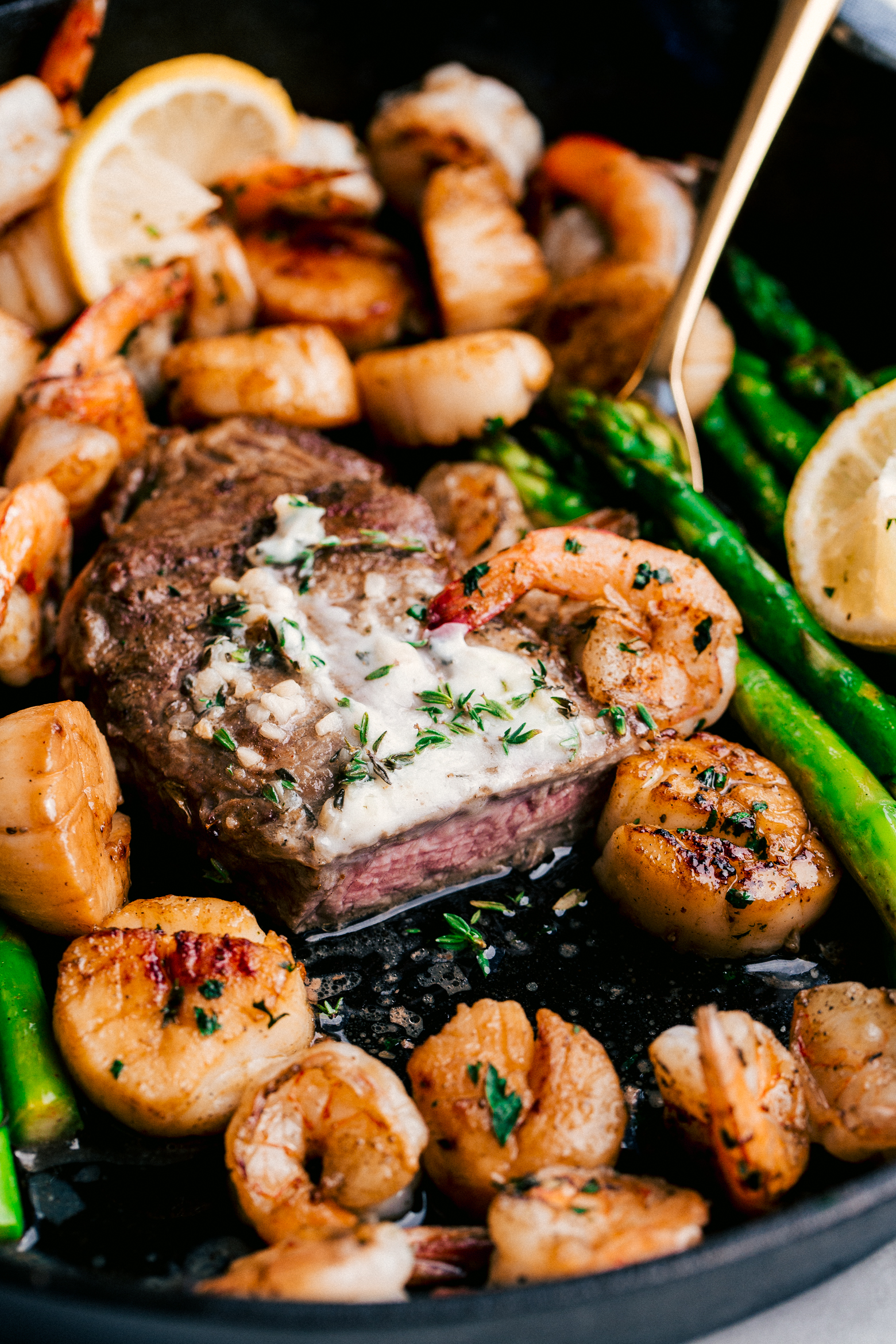 surf and turf made in a one pot with tender steak and juicy shrimp served with garlic butter and asparagus, by The Food Cafe.