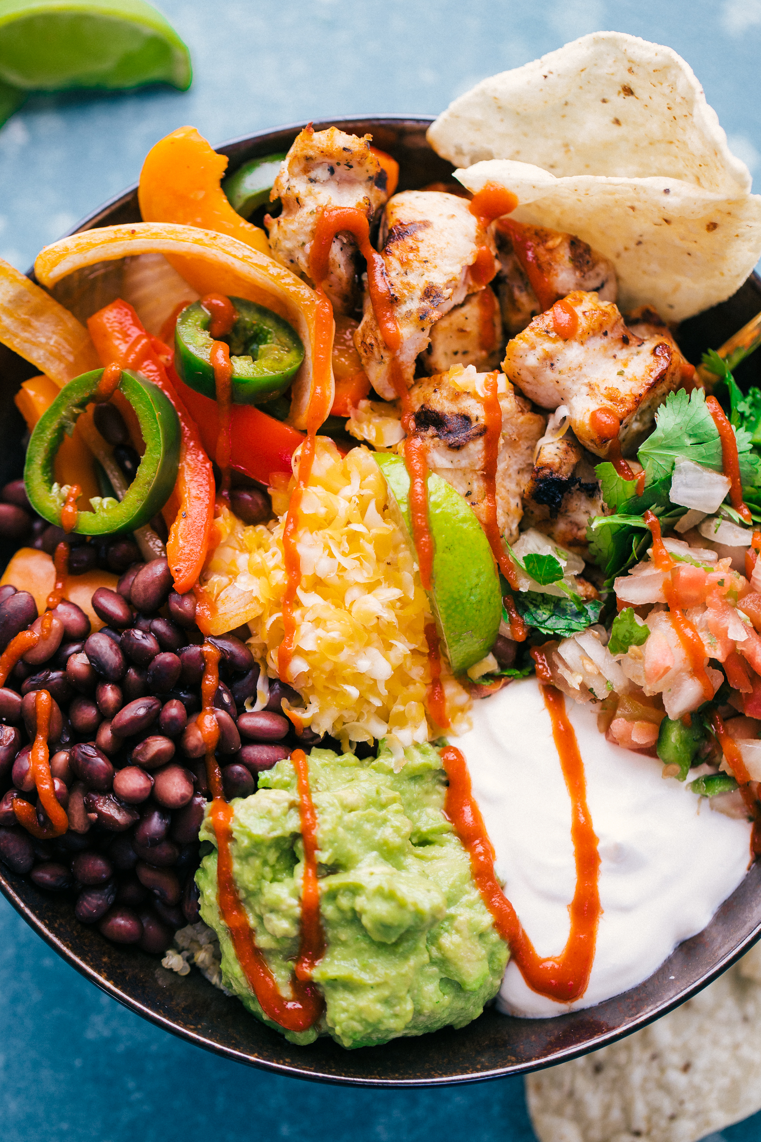 Burrito Bowl with quinoa, chicken, cheese, guacamole, black beans, and sour cream for a delicious weeknight meal, by The Food Cafe.