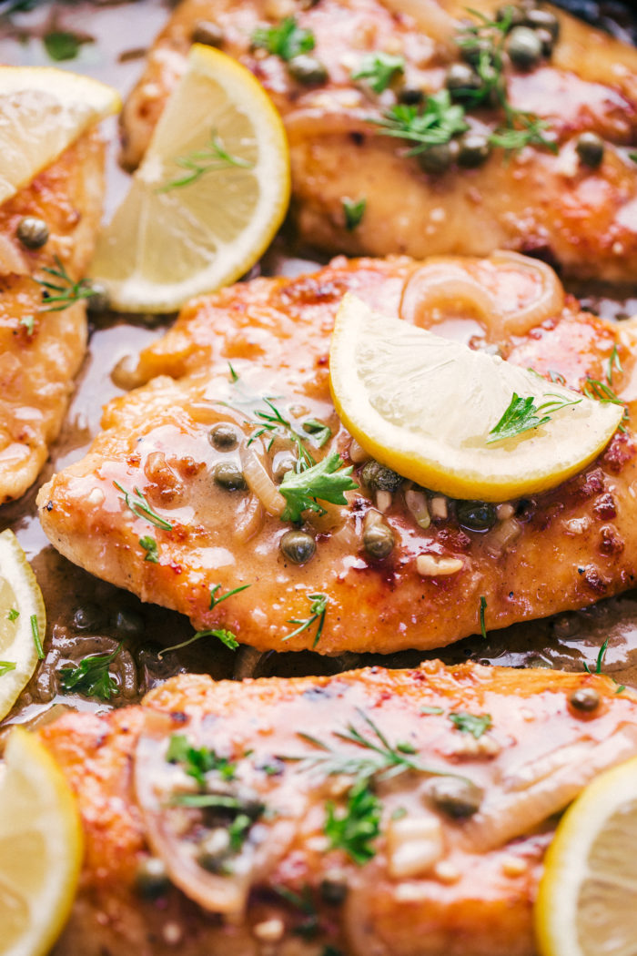 chicken piccata recipe served with slices of lemon and fresh chopped parsley on top by The Food Cafe.