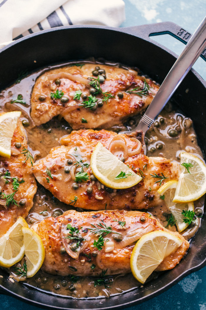 A blue background with a cast iron skillet serving creamy lemon garlic chicken piccata, by The Food Cafe.