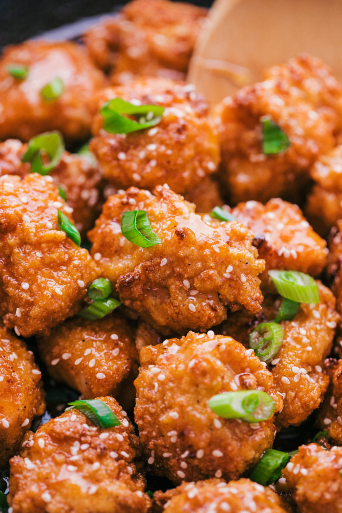 honey sriracha chicken topped with diced green onions and white sesame seeds, by The Food Cafe