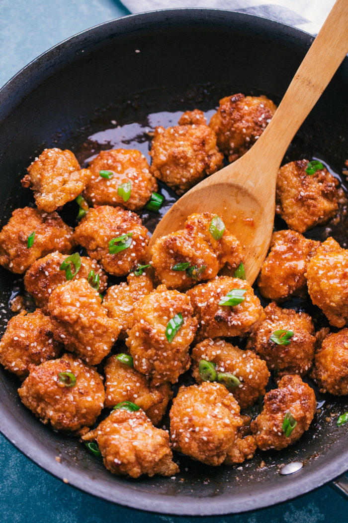 honey chicken cooked up in a black skillet and perfect for an easy week night meal by The Food Cafe.