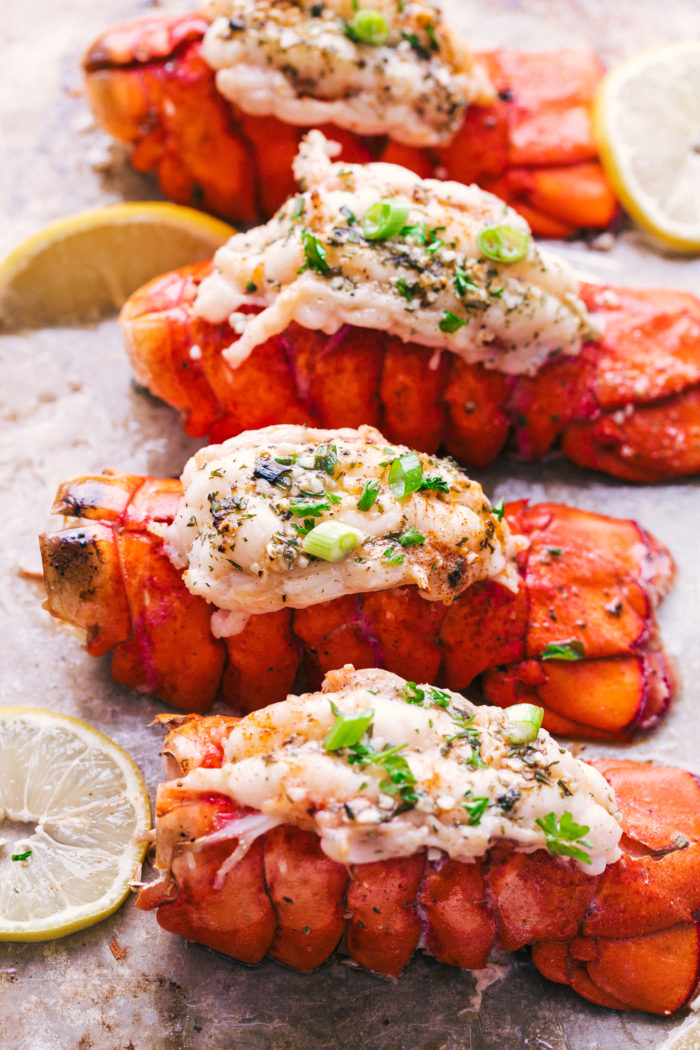 Lobster tails lined up on a baking sheet topped with melted butter and diced green onions, by The Food Cafe.