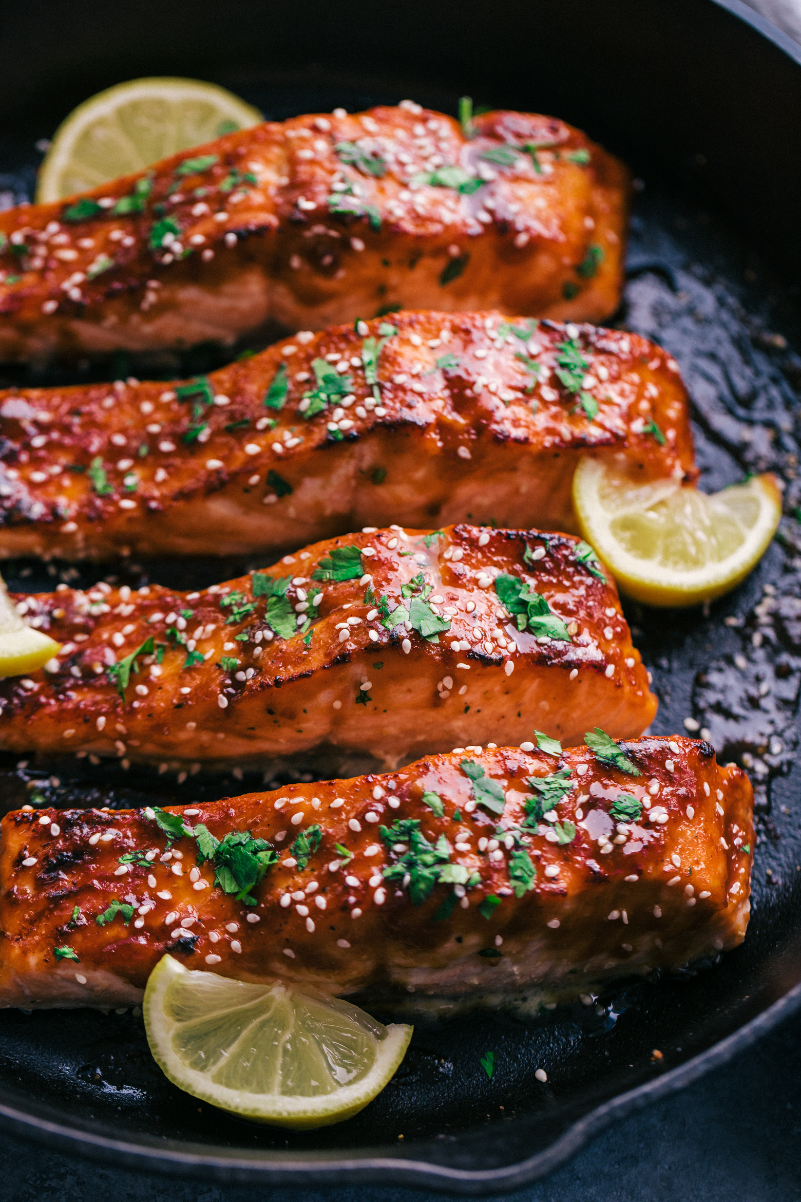 maple glazed salmon in a cast iron skillet topped with fresh chopped herbs and slices of lemon by The Food Cafe