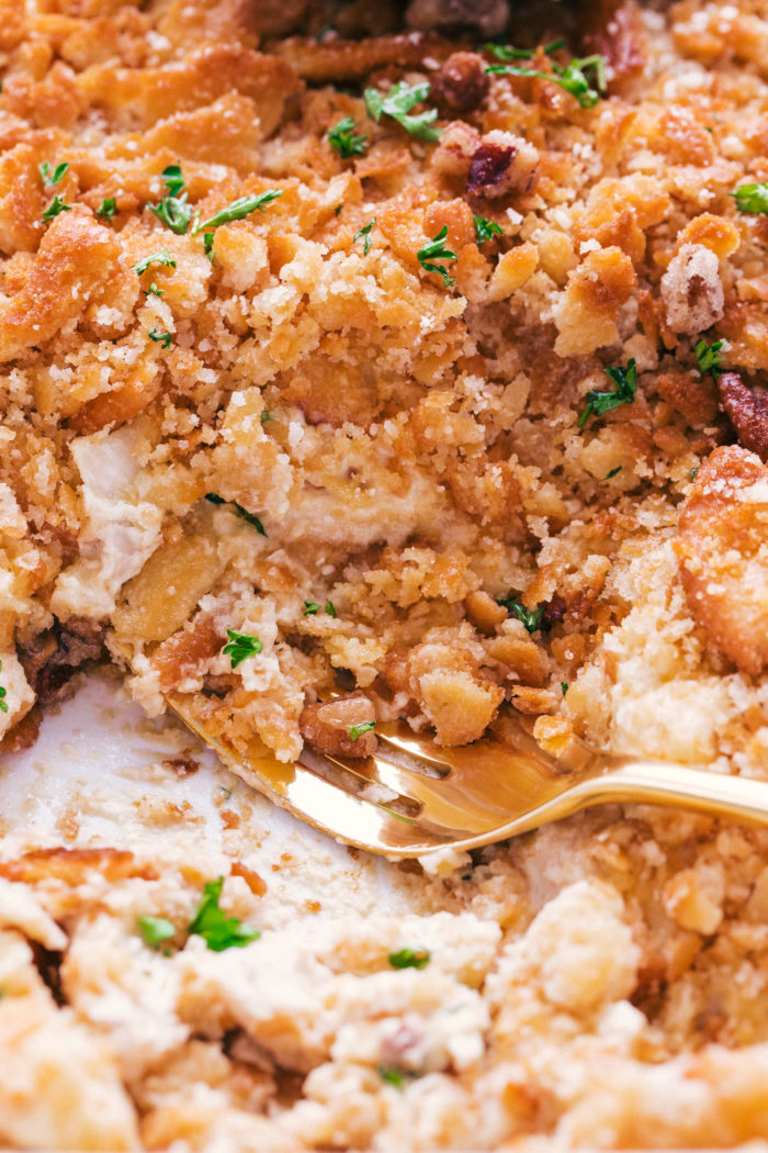 Ritz chicken casserole topped with chopped ritz crackers and served on a plate with a gold fork, by the food cafe.