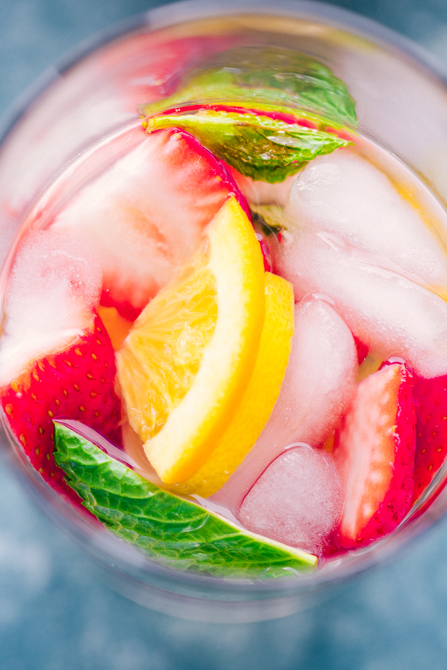Strawberry Detox Water with fresh lemon wedges, fresh cut strawberries, and mint leaves, a great cleanse by The Food Cafe.