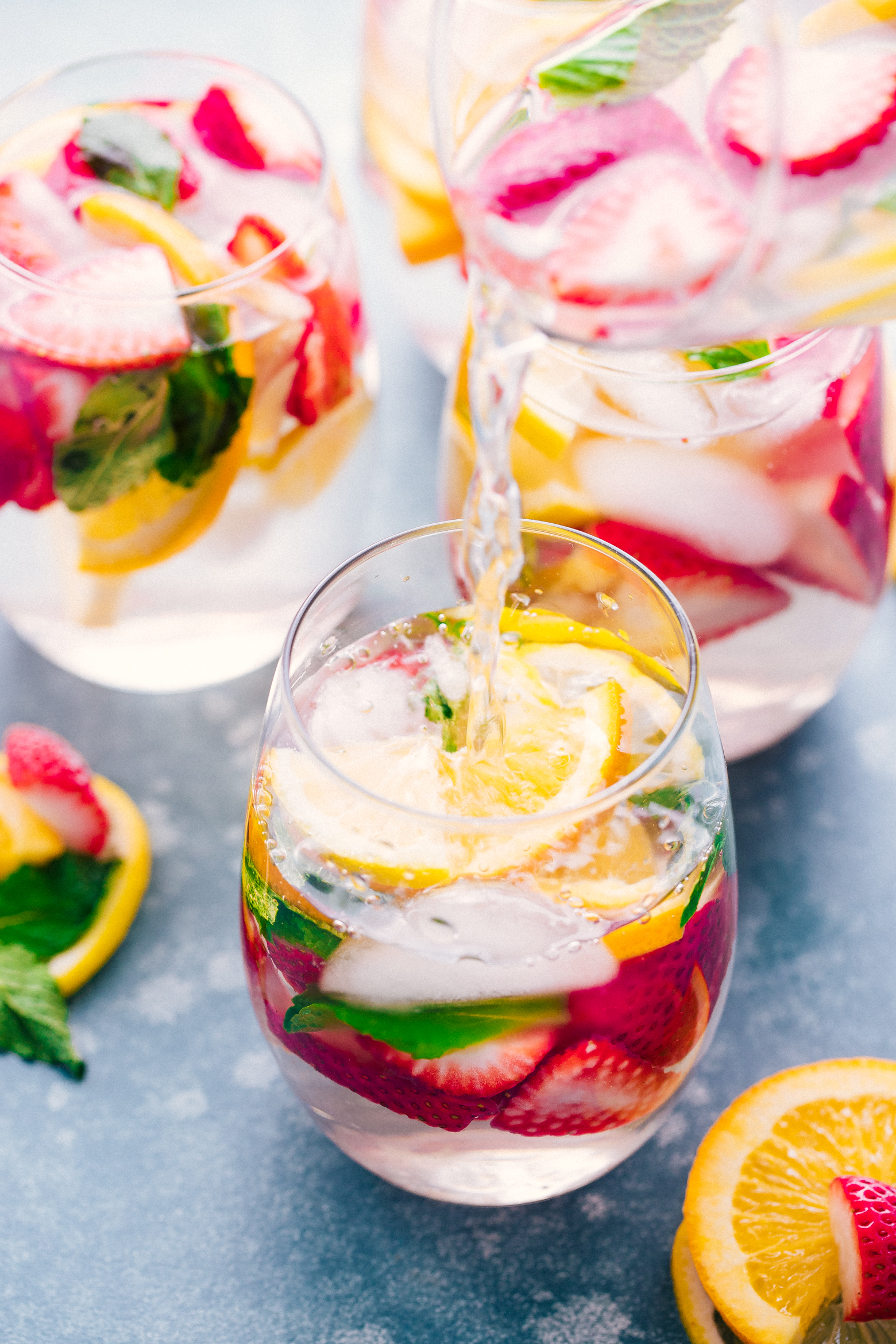 Detox Water being poured into a glass with strawberries, lemon, and mint for a healthy burst to your body, by The Food Cafe.