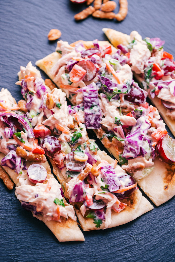 Chicken Salad that is made with grapes with a thai flavor on a black cutting board served on flat bread by The Food Cafe.