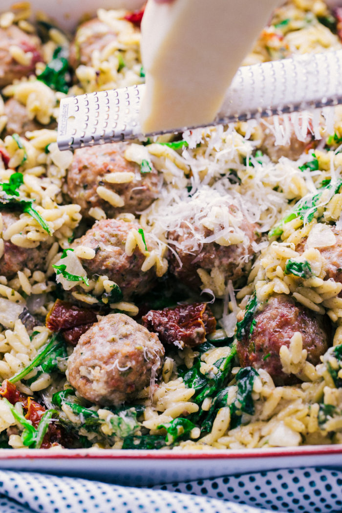 Meatball casserole topped with parmesan cheese, chopped parsley and so much more, by The Food cafe.