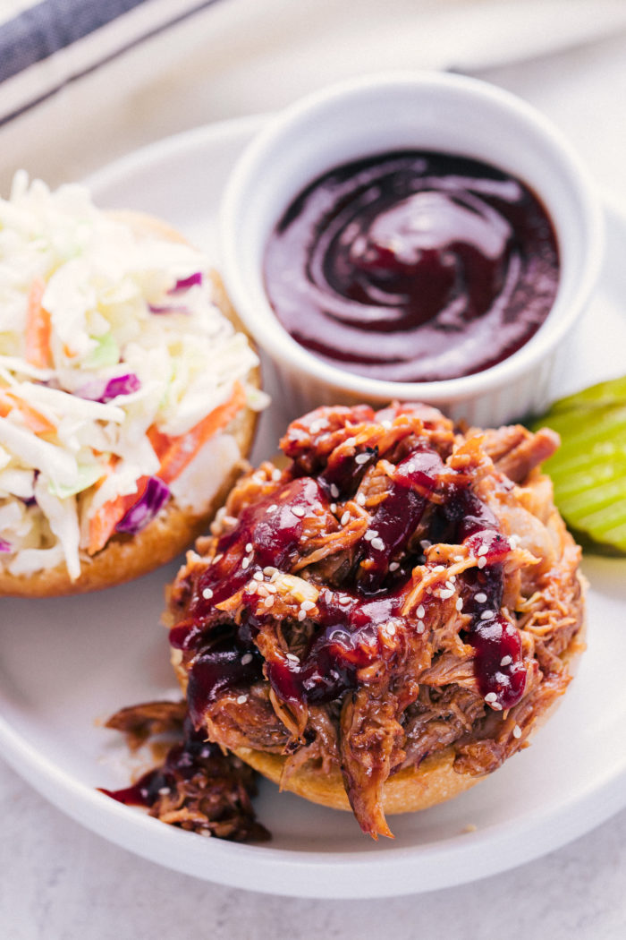 BBQ Pulled Pork loaded on a hamburger bun served with bbq sauce and a side of coleslaw by The Food Cafe.