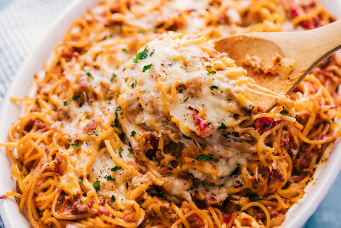 baked spaghetti in a white baking dish with a serving spoon.