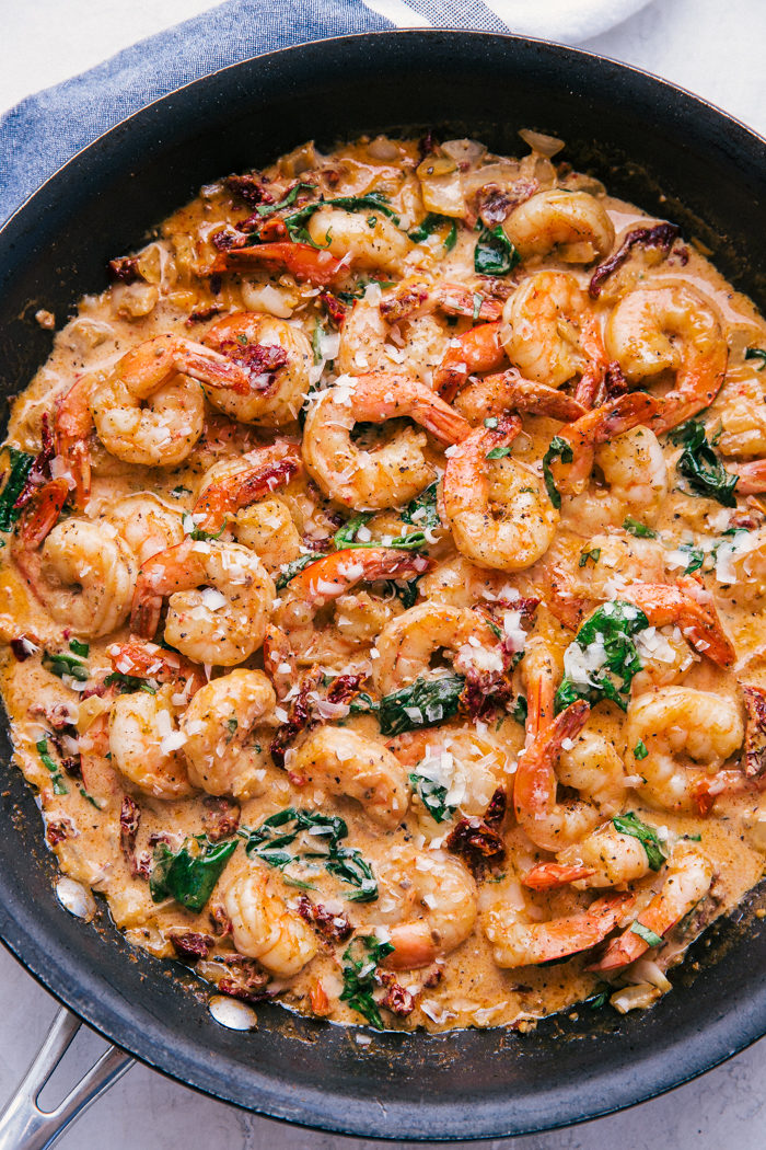 Garlic Shrimp cooked in a creamy sun dried tomato sauce in a skillet with cooked spinach and topped with parmesan cheese by The Food Cafe